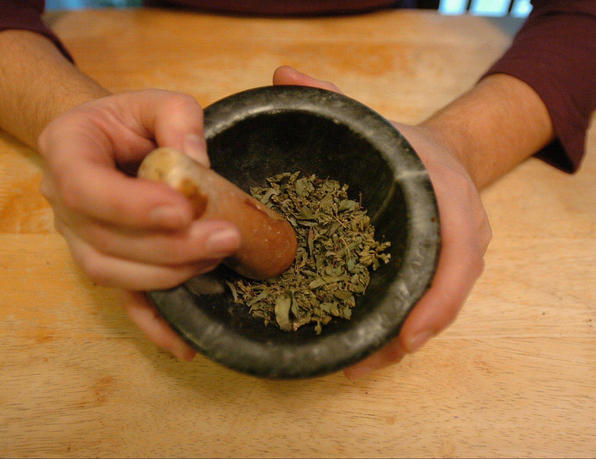 Cote Garceau-Saez grinds herbs for a tea mix she uses as a home remedy.