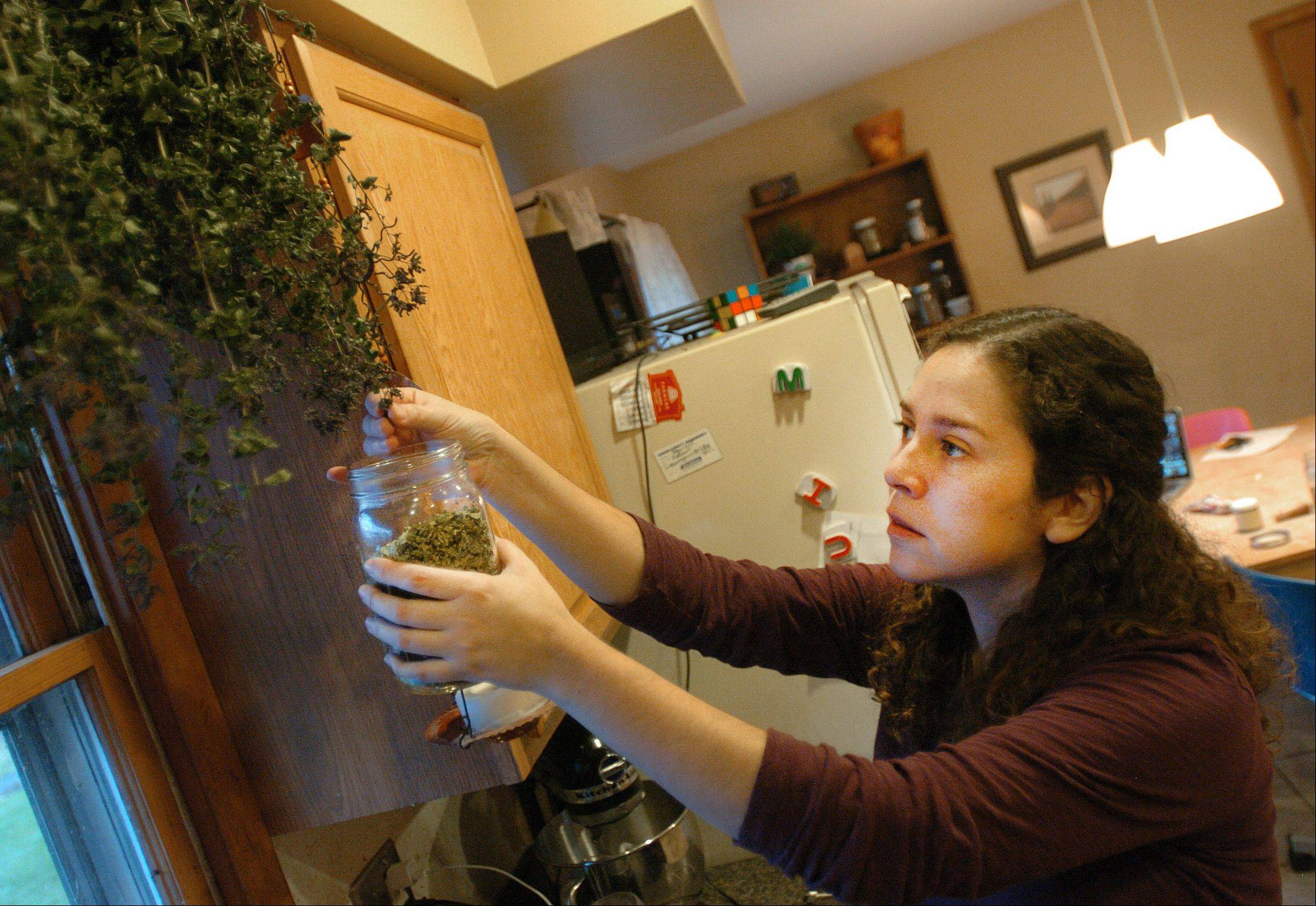 Cote Garceau-Saez pulls dried herbs from her kitchen window.