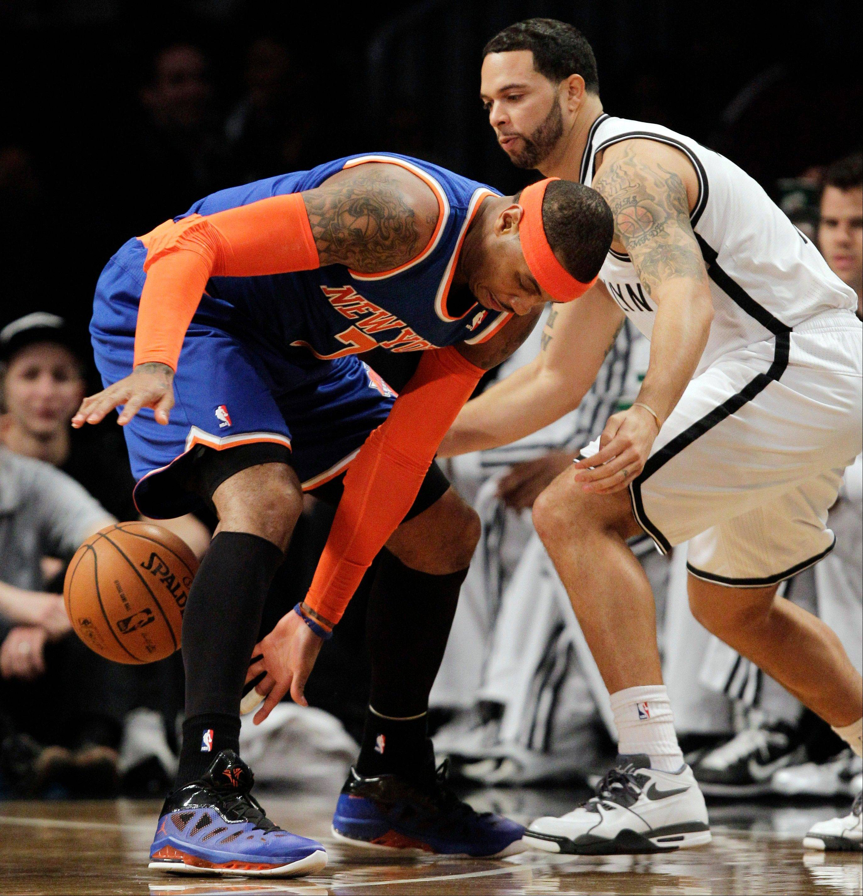 New York Knicks forward Carmelo Anthony loses the ball as Brooklyn Nets guard Deron Williams defends Tuesday during the first half at the Barclays Center in New York.