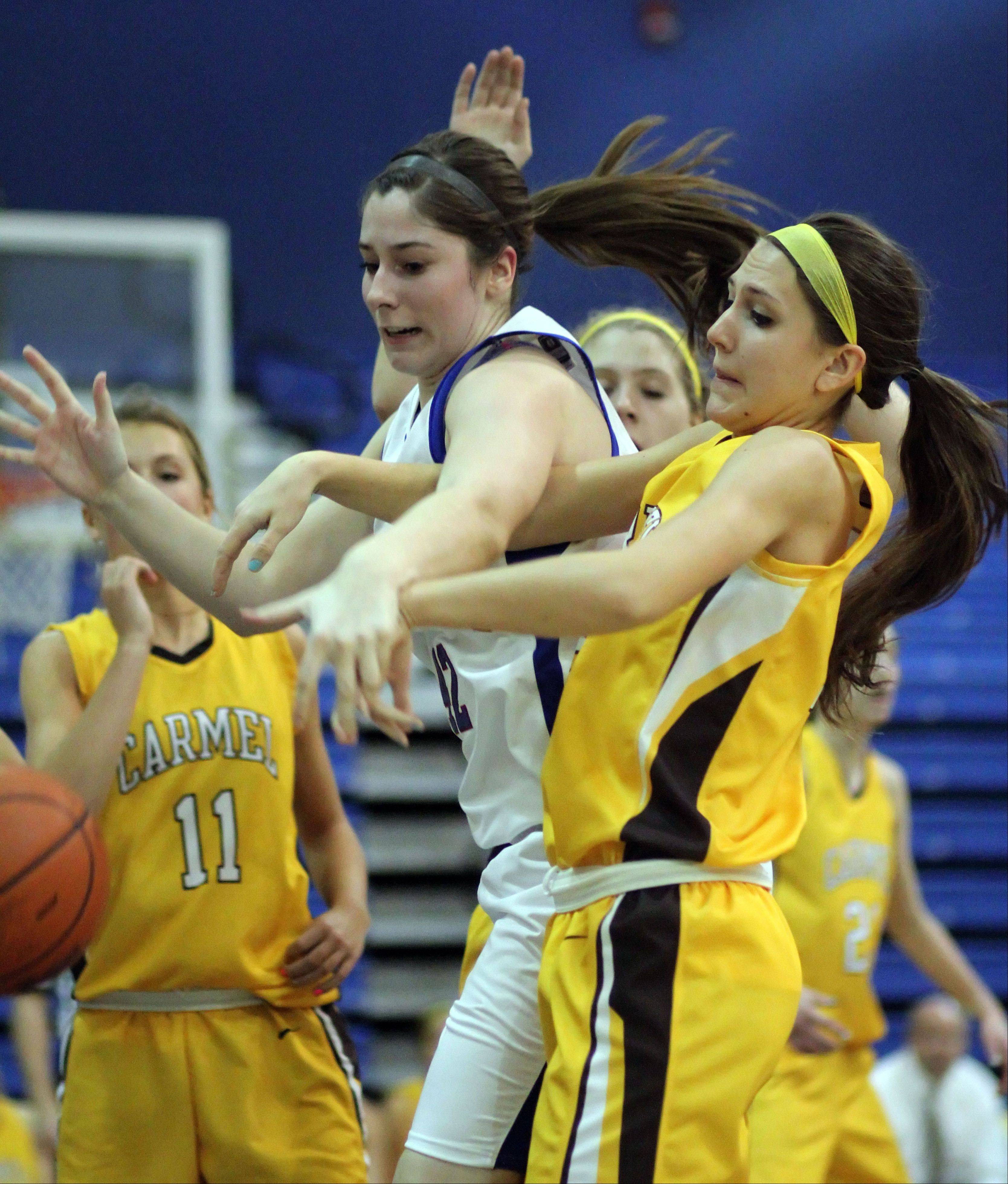 Lakes' Therese McMahon, left, and Carmel's Paige Gauthier fight for the rebound during Monday's basketball game in Lake Villa.