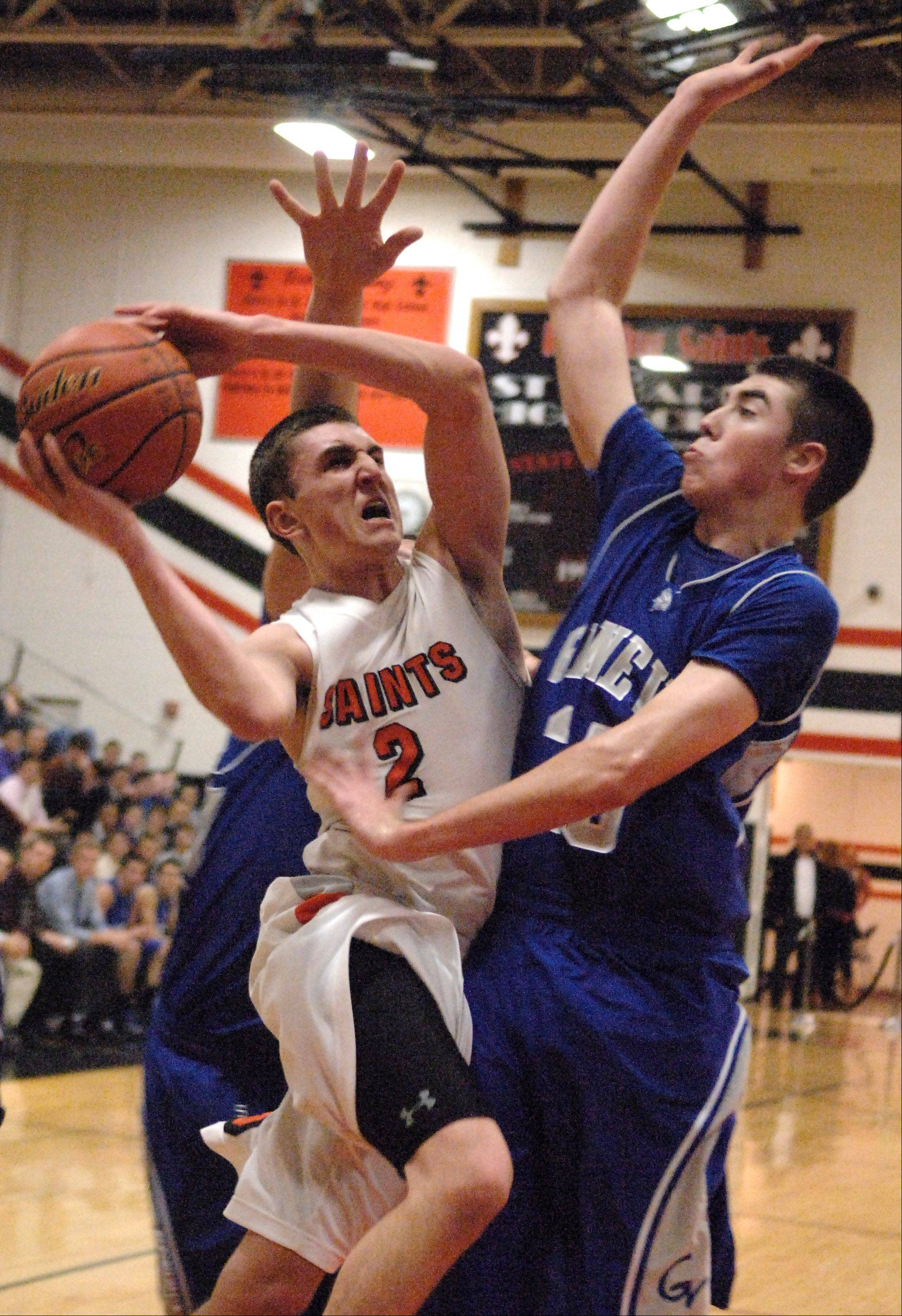 St. Charles East's Dom Adduci drives to the lane and scores despite a Geneva double-team effort Friday in St. Charles.