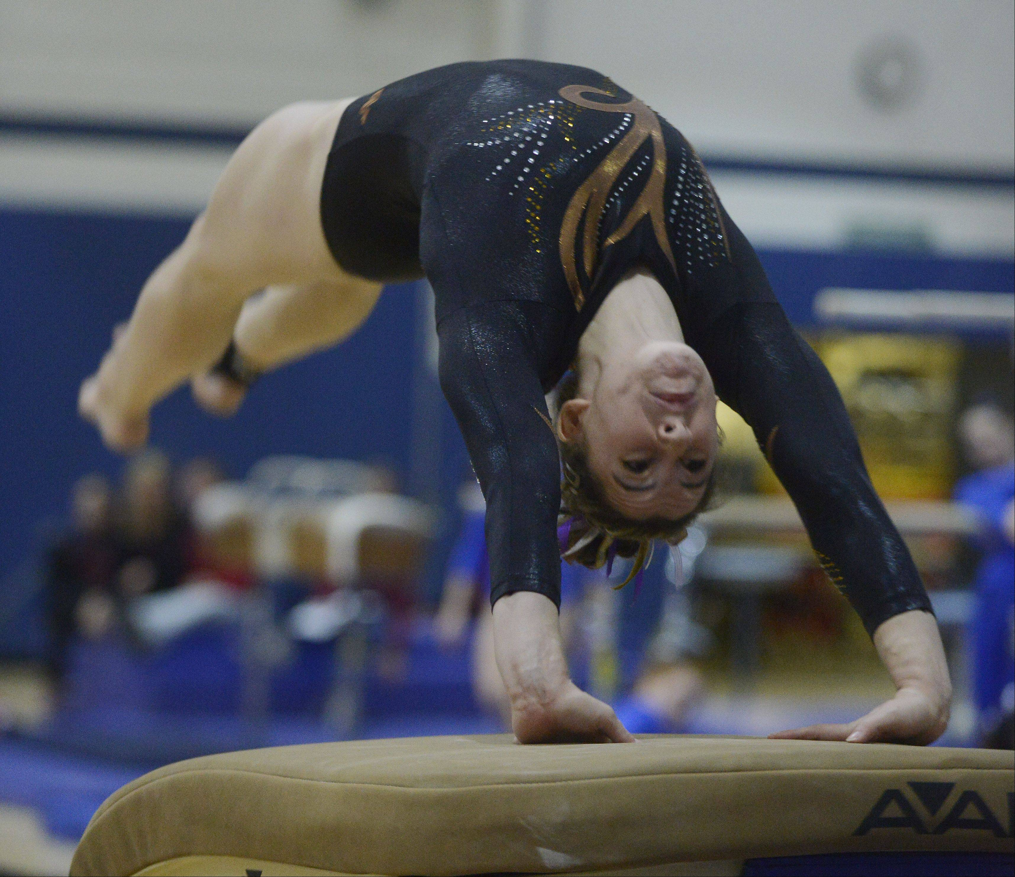 Carmel's Lauren Feely competes on the vault during the Conant girls gymnastics invite Saturday.