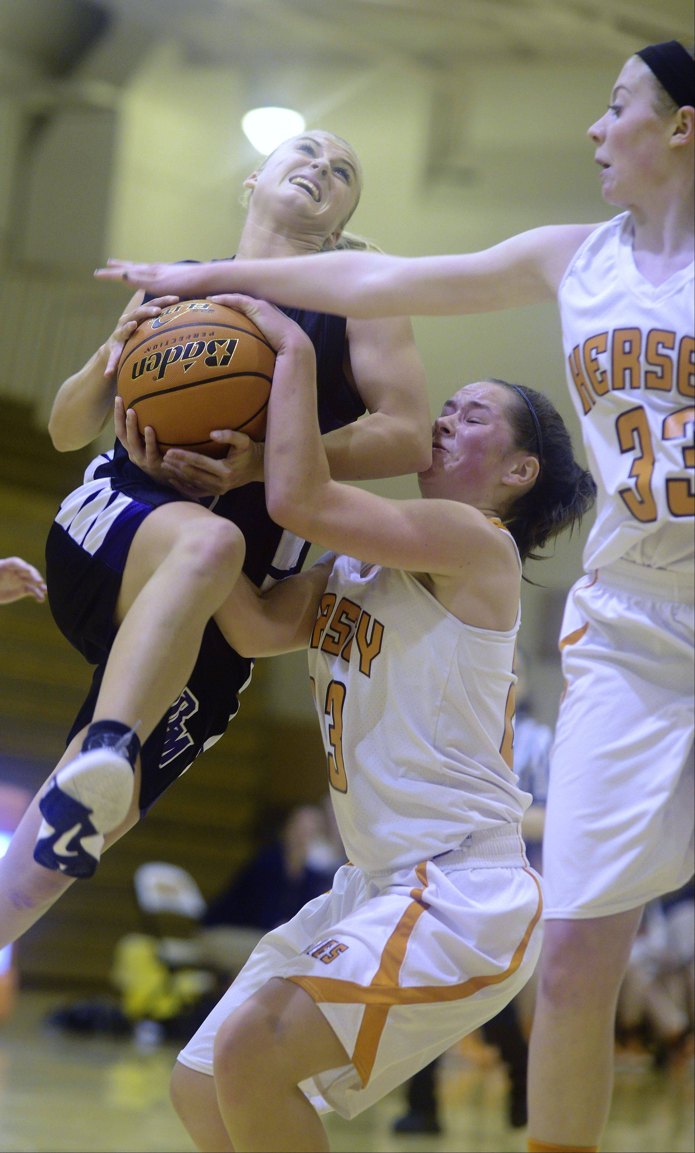 Rolling Meadow's Jackie Kemph, left, gets fouled as she heads to the basket against Hersey defenders Casey Weyrich, middle, and Ashley Raulli.