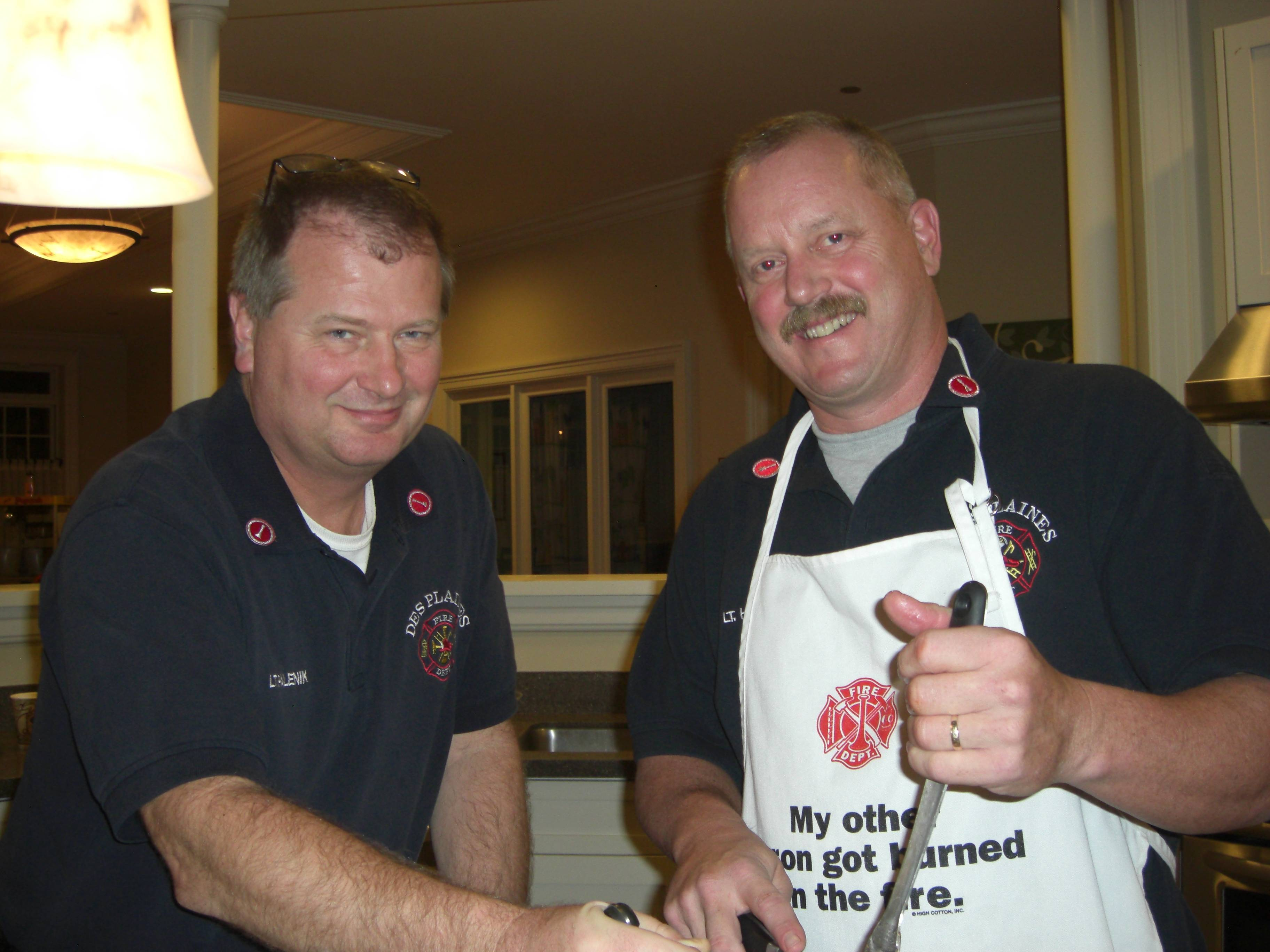(pictured) Des Plaines Fire Department Lieutenant and Firefighters Union President Jim Hall (right) and Fire Lieutenant Ken Palenik (left) pose for a photograph as Des Plaines Firefighters and spouses help prepare a home-cooked meal for families at the Ronald McDonald House, Chicago, on November 7, 2012.