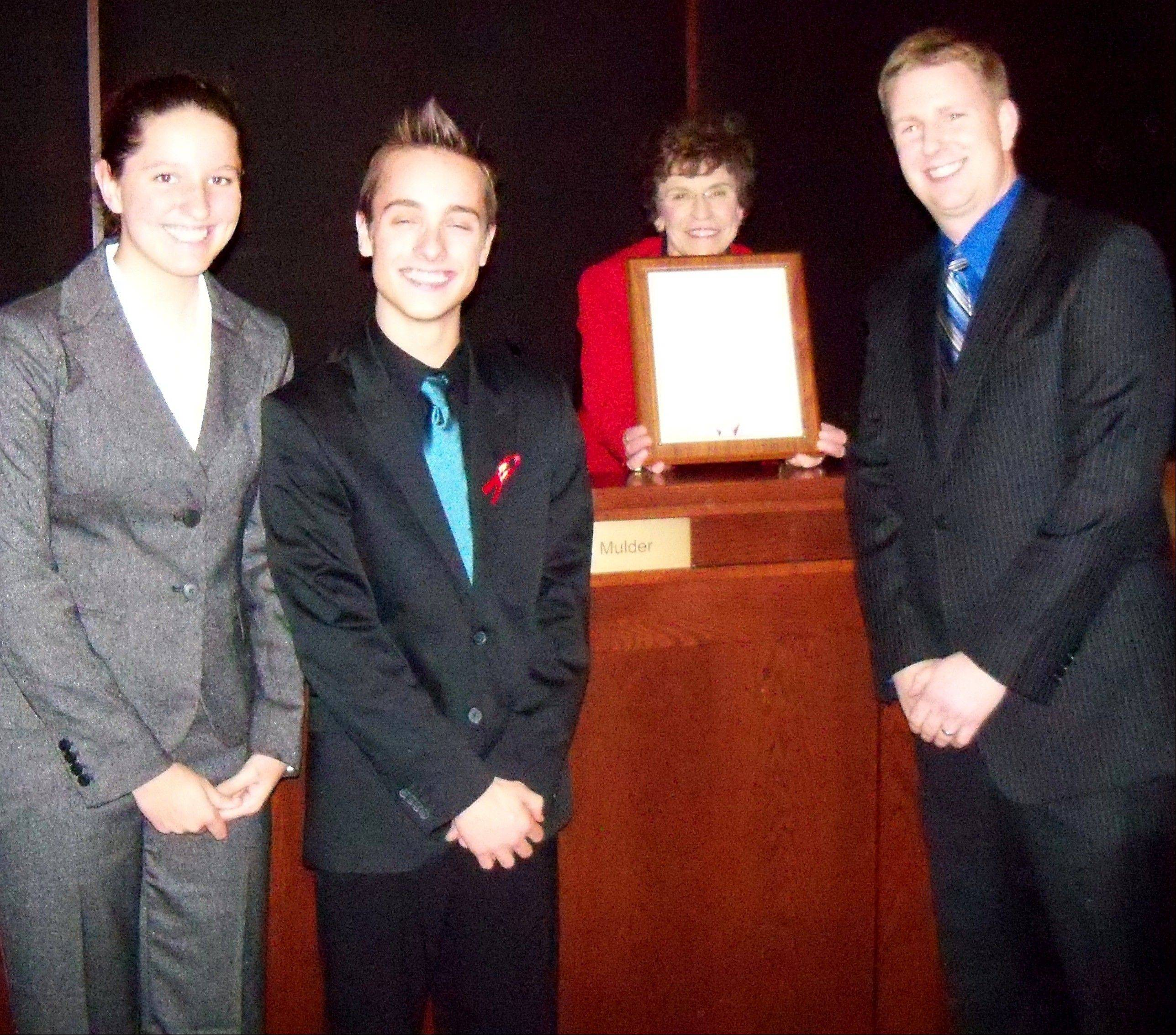 Accepting the Proclamation of Recognition from Arlington Heights Mayor Arlene J. Mulder, center, are Prospect Marching Knights' Drum Majors (student directors) Destiny Duraj, far left, and Ted Marzolf, and director of bands Chris Barnum, right.