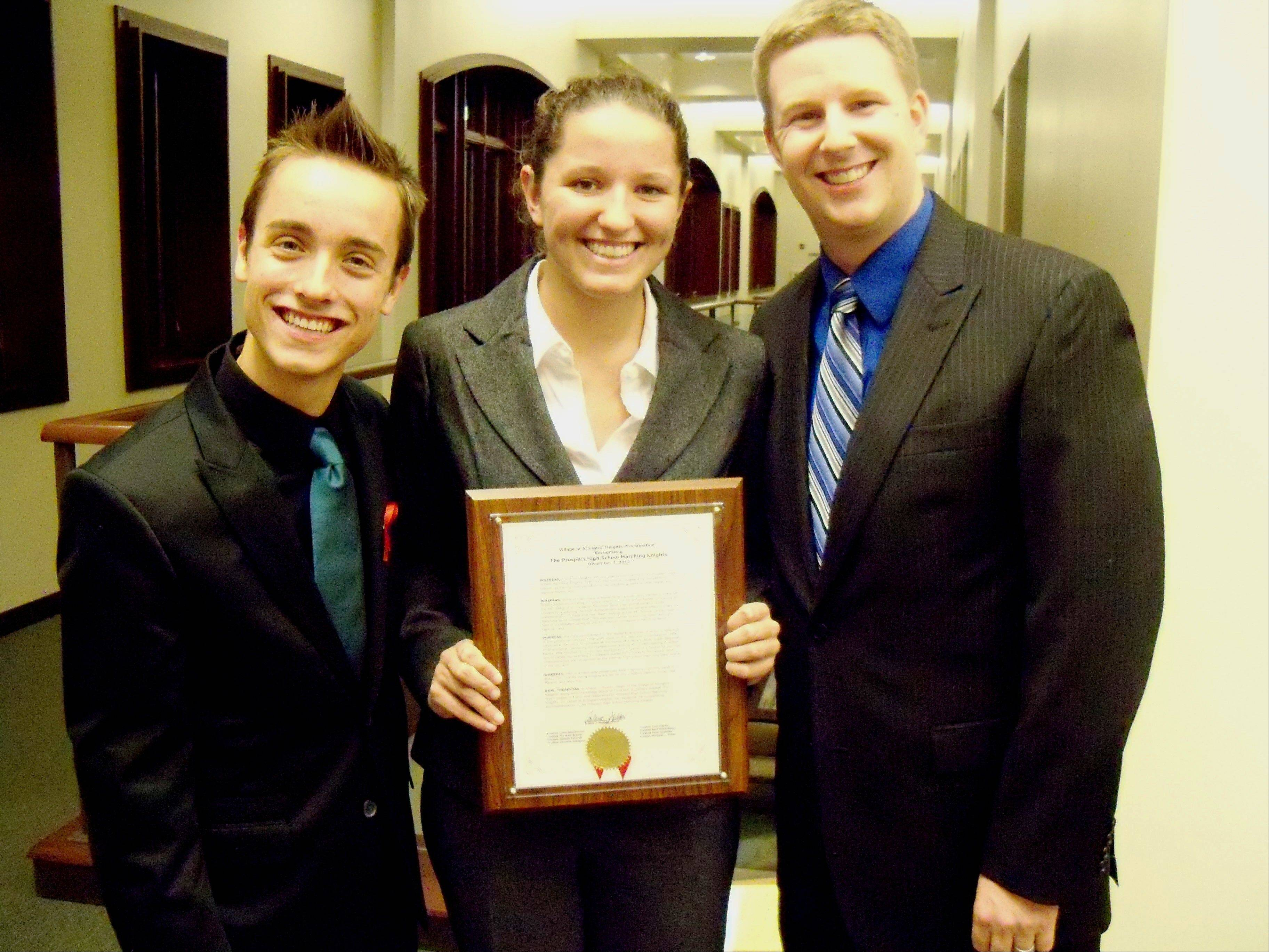 Prospect Marching Knights Drum Majors Ted Marzolf, left, and Destiny Duraj, center, display their Proclamation plaque with PMK director Chris Barnum.