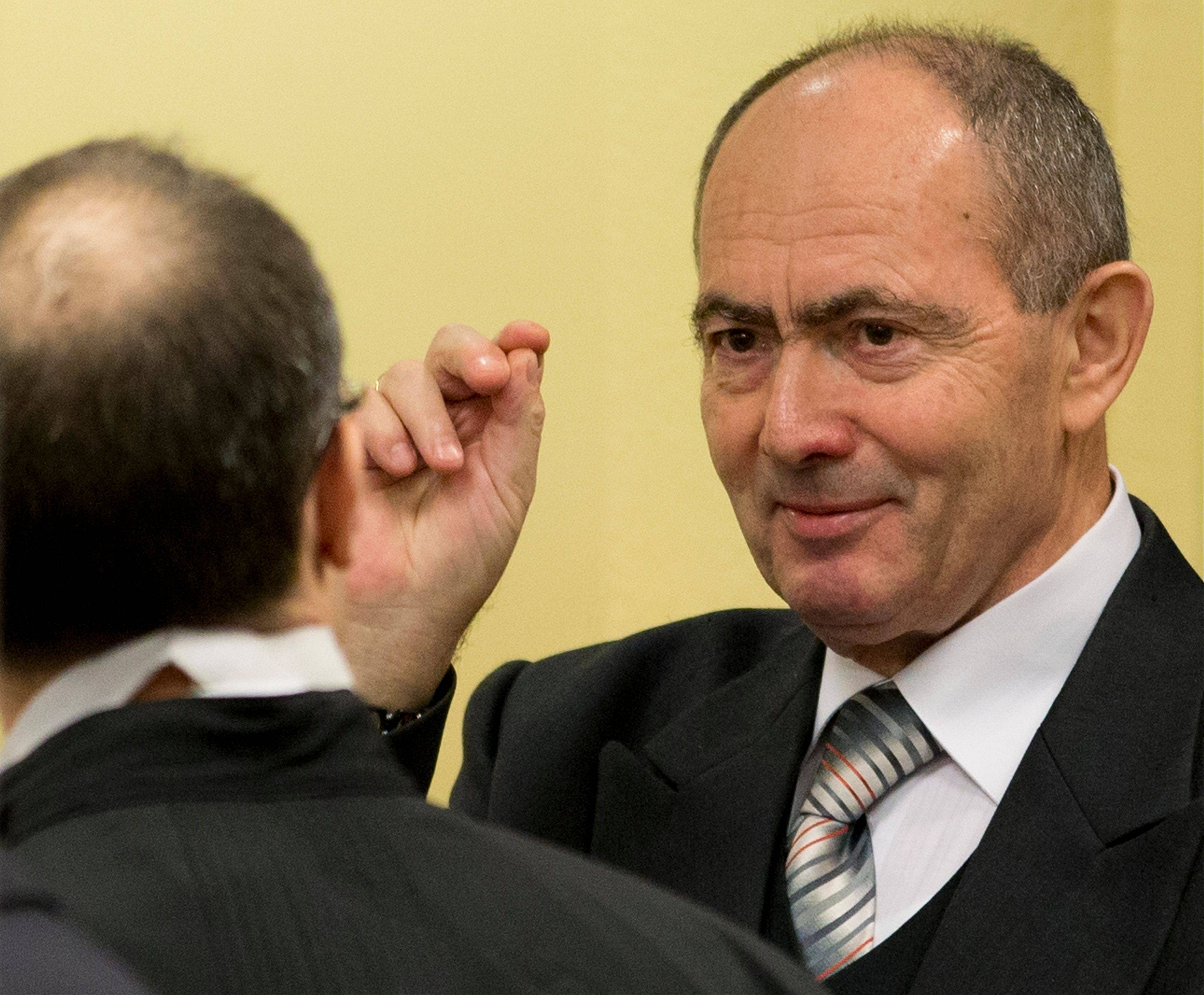 Zdravko Tolimir, right, a former high-ranking Bosnian Serb army officer charged with crimes including genocide in the 1995 Srebrenica massacre, crosses himself as he waits for the Yugoslav war crimes tribunal to deliver its judgment. The tribunal convicted him and sentenced him to life imprisonment.