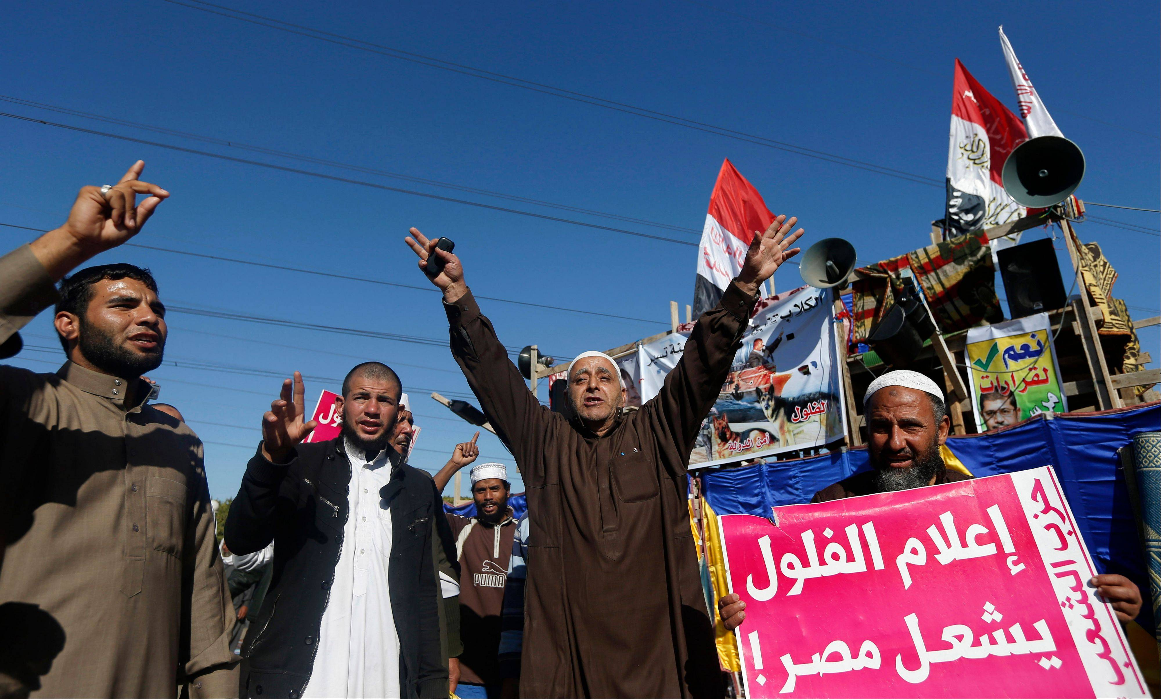 "Islamist protesters supporting Egyptian President Mohammed Morsi chant slogans in front of the Media City complex in Giza, Egypt, Wednesday, Dec. 12, 2012. The Arabic sign at right reads, ""journalist remnants will destroy Egypt."" An Egyptian opposition alliance urged supporters on Wednesday to vote ""No"" in the referendum on a disputed constitution but said it may still boycott if its conditions are not met."