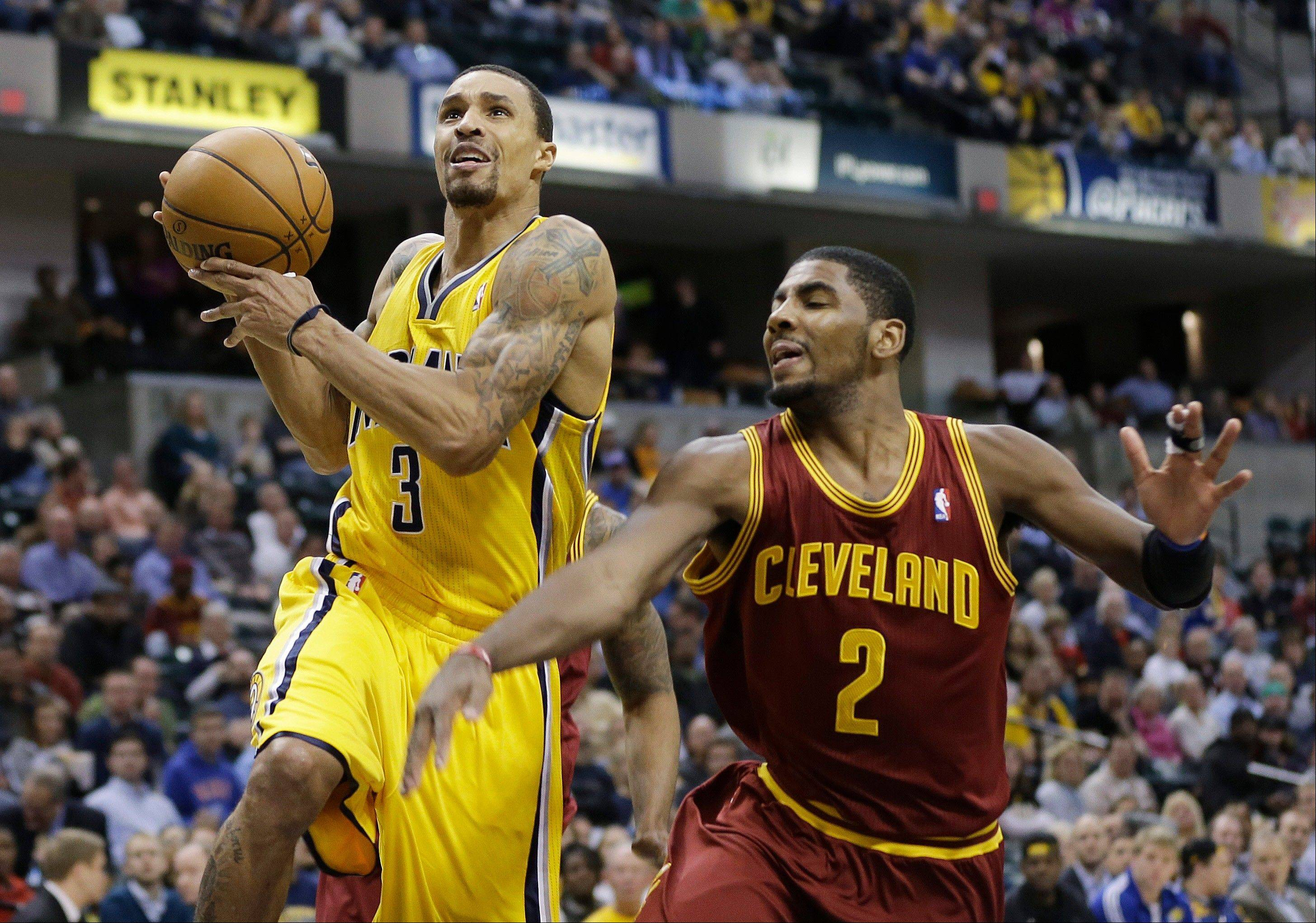 The Indiana Pacers' George Hill is fouled by Cleveland Cavaliers guard Kyrie Irving as he goes up for a shot Wednesday during the second half in Indianapolis. The Pacers defeated the Cavaliers 96-81.