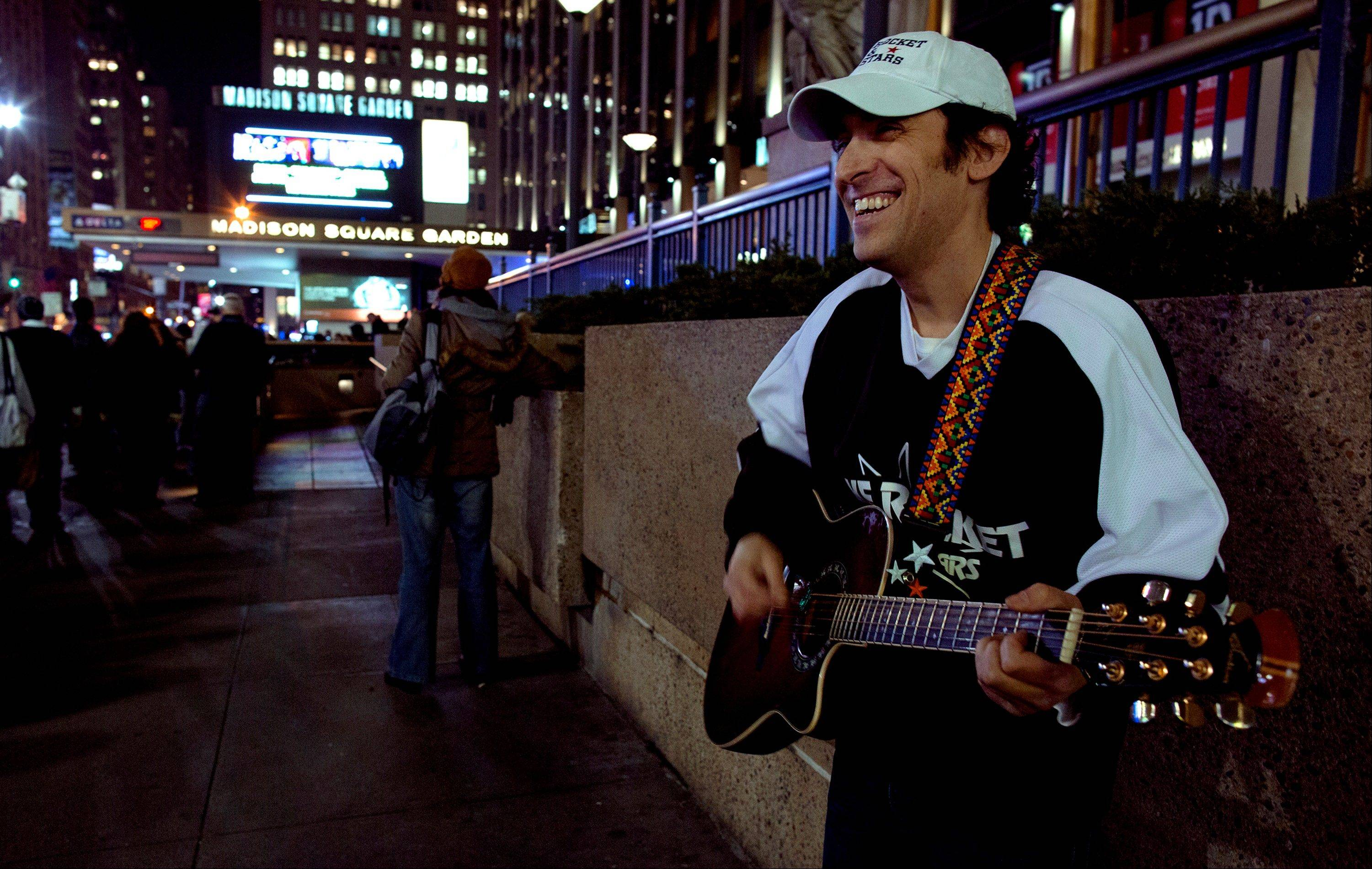 "Musician Mike Rocket of New York entertains people gathering Wednesday before the ""12-12-12"" benefit concert at Madison Square Garden in New York."