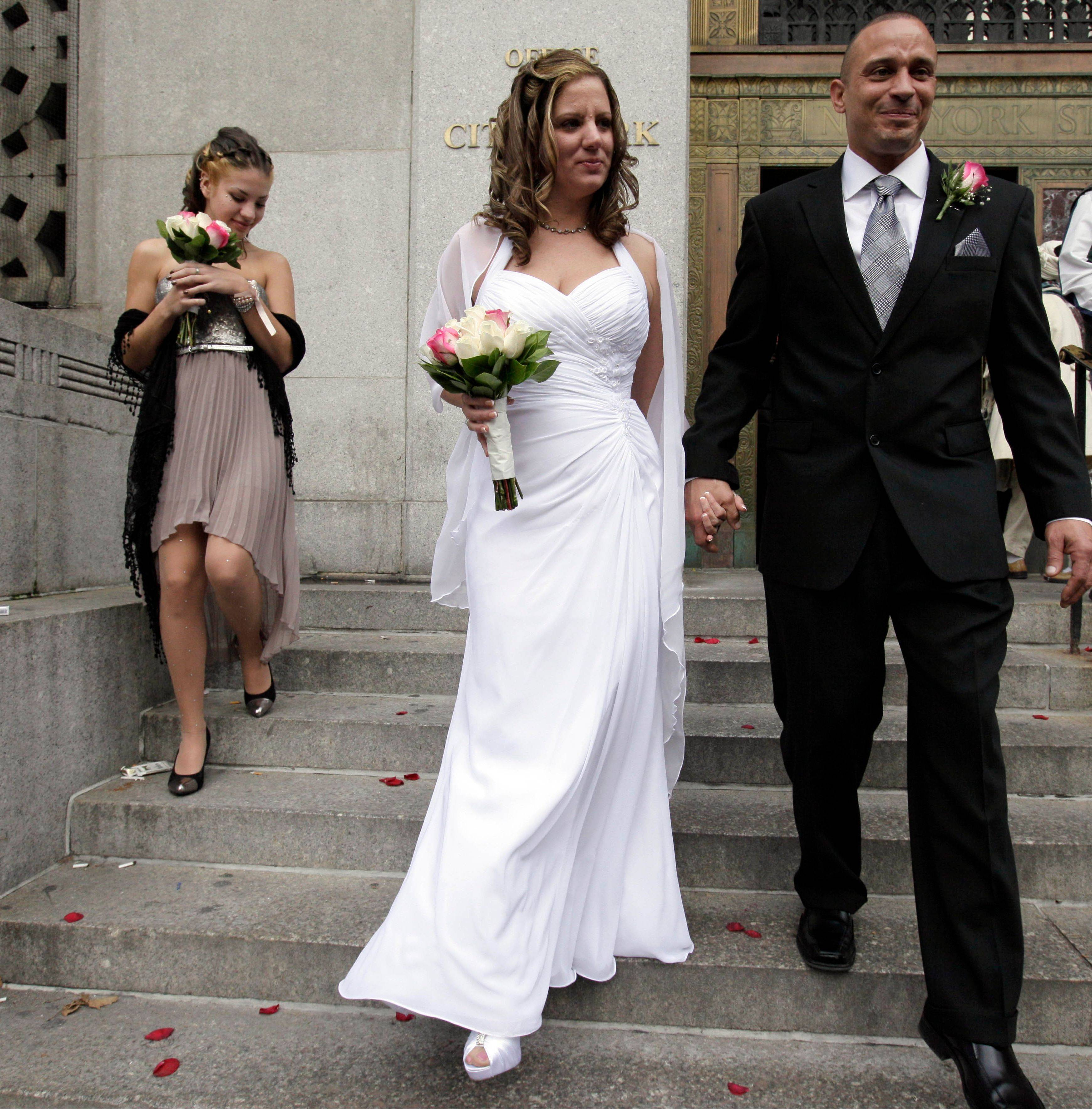 Harold, right, and Parcia Hochhauser, of the Brooklyn borough of New York, and her daughter, Pricilla Pardo, left, leave the Office of the City Clerk in New York Wednesday after their wedding.