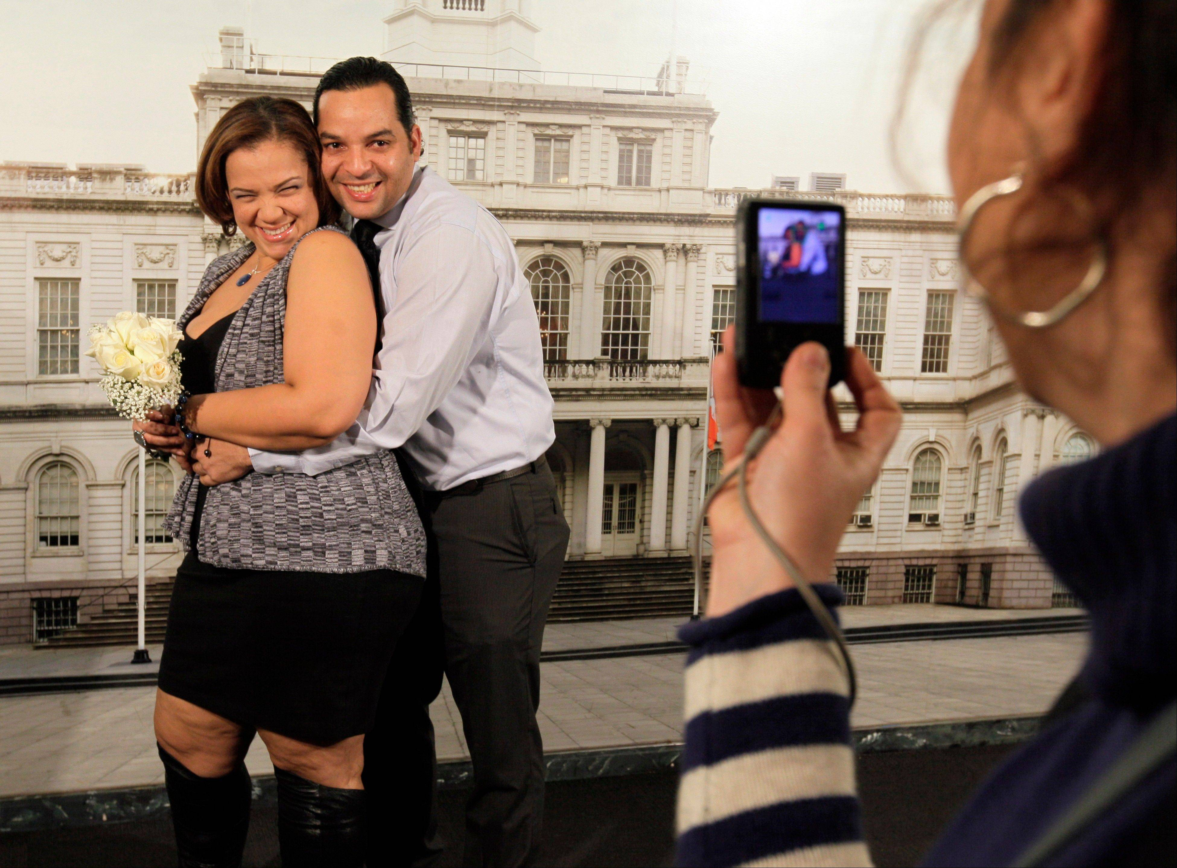 Francisco Mena, and his new wife, Carolina Mena, of the Washington Heights neighborhood of New York, pose Wednesday for photos in the Office of the City Clerk in New York after their wedding.