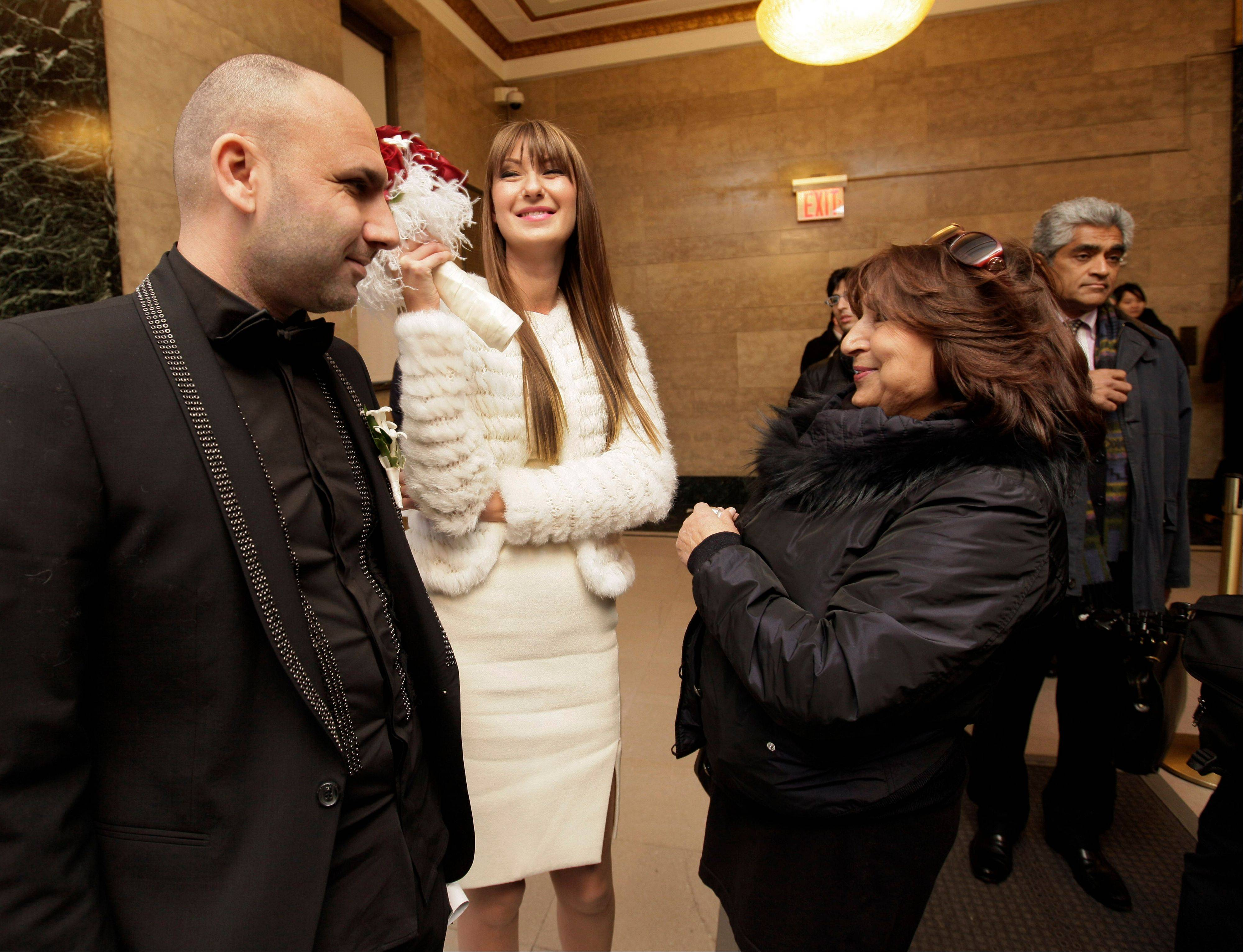 Gleb Bukin, left, and his fiancee Kate Val, of Fort Lee, N.J., center, wait Wednesday with his mother, Mila Bukin, to be married in the Office of the City Clerk in New York.