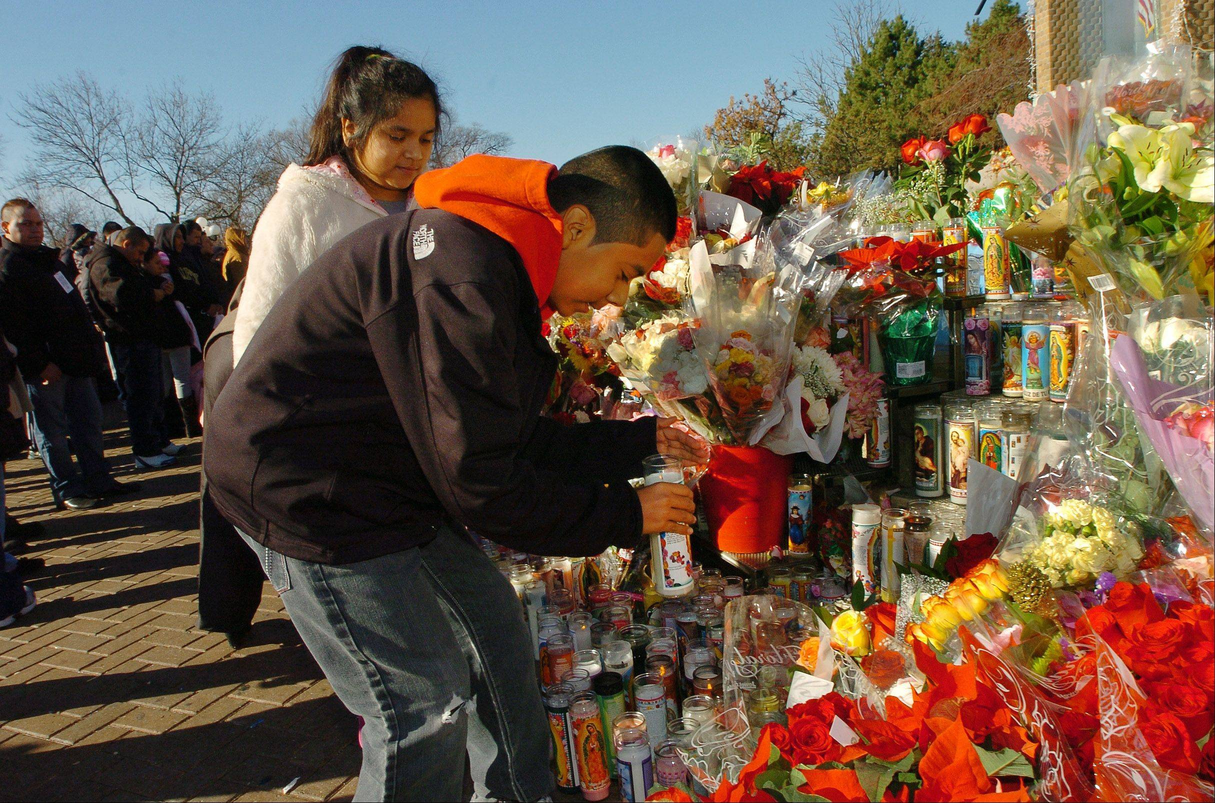 Maurilio Barrera of Chicago and his sister Erica light a candle at the Our Lady of Guadalupe shrine in Des Plaines.