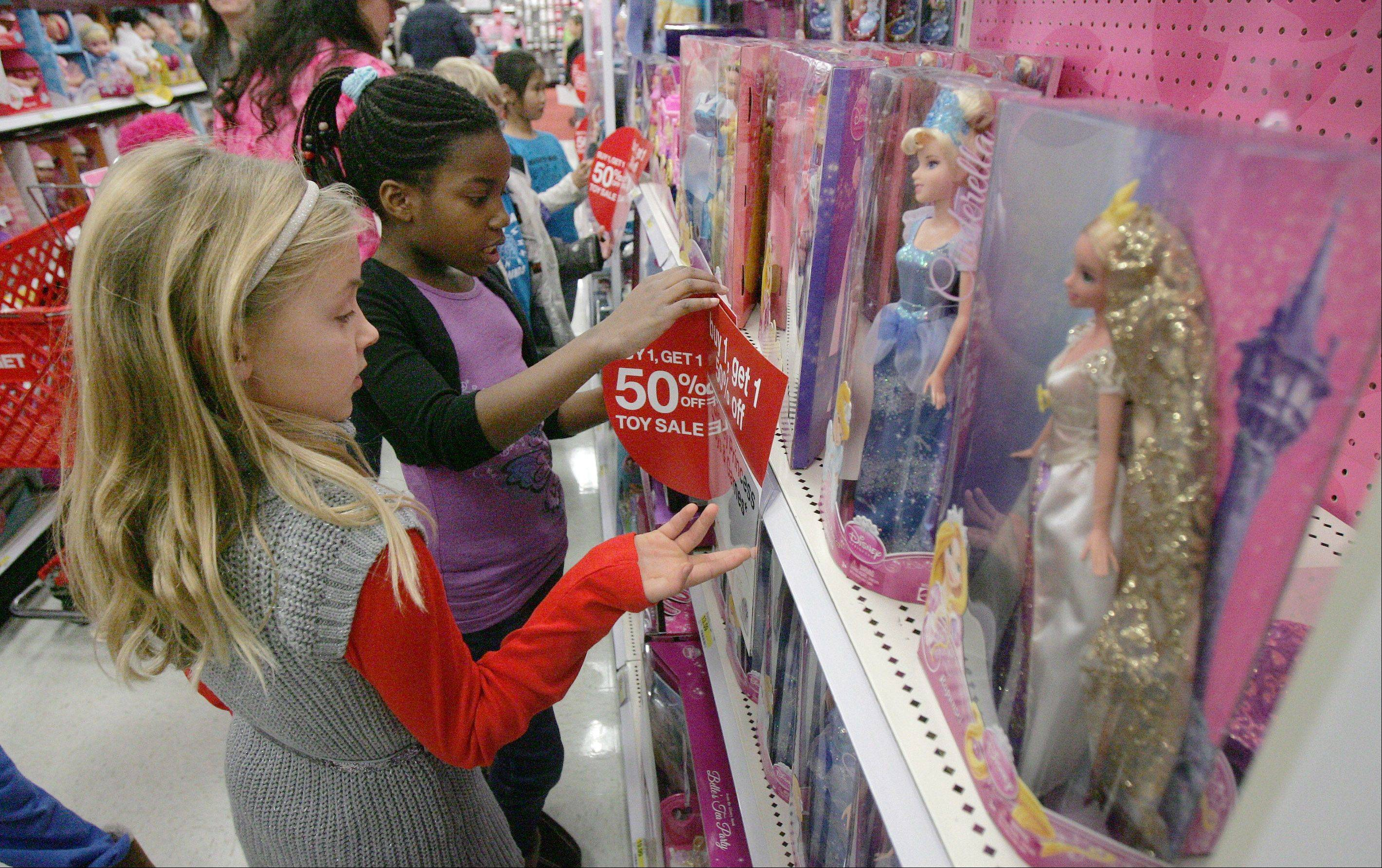 Fremont School third-graders Payton Regan, left, and Bethel Mensah look at dolls as students shop for clothes and toys Wednesday at Target in Mundelein to help needy families for the holidays. It was part of the school's Sponsor A Family program, which helps provide gifts for 30 children.