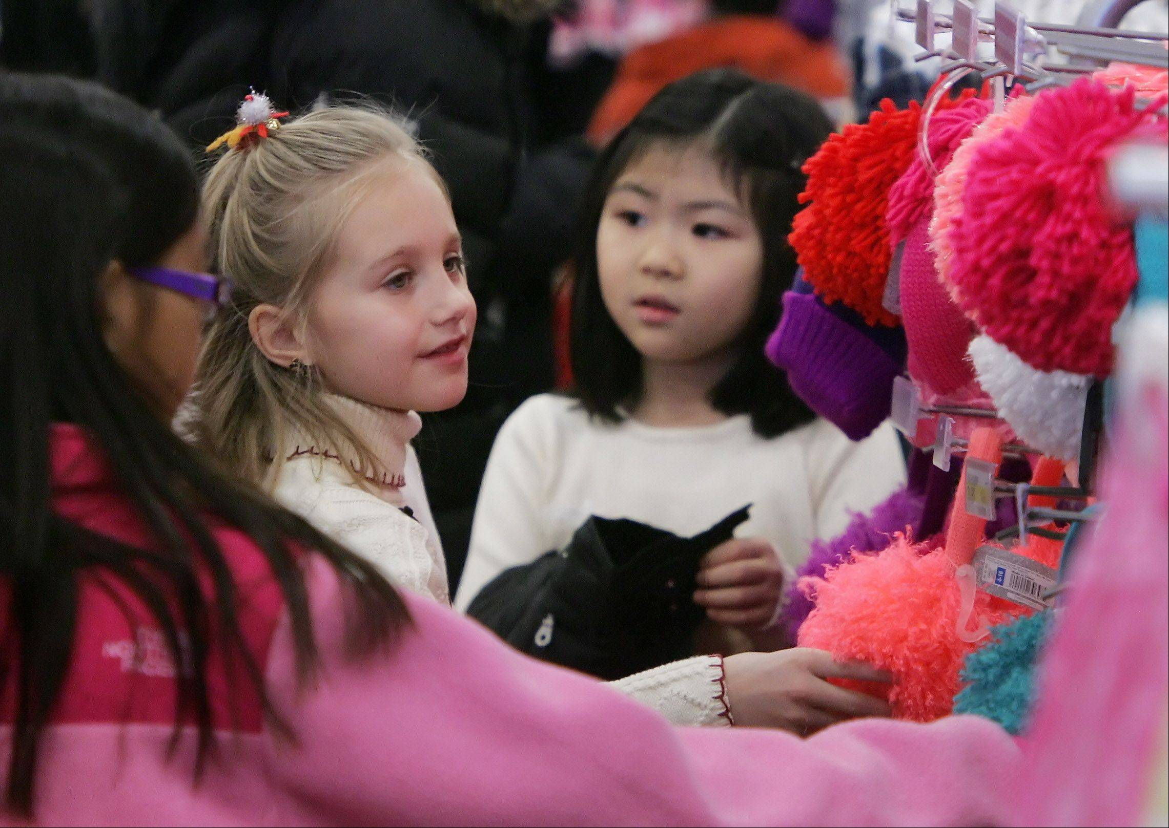 Fremont School third-graders Jordi Landry, left, and Grace Kim look at clothing accessories as students shop for clothes and toys Wednesday at Target in Mundelein to help needy families for the holidays. The event was part of the school's Sponsor A Family program, which helps provide gifts for 30 children.