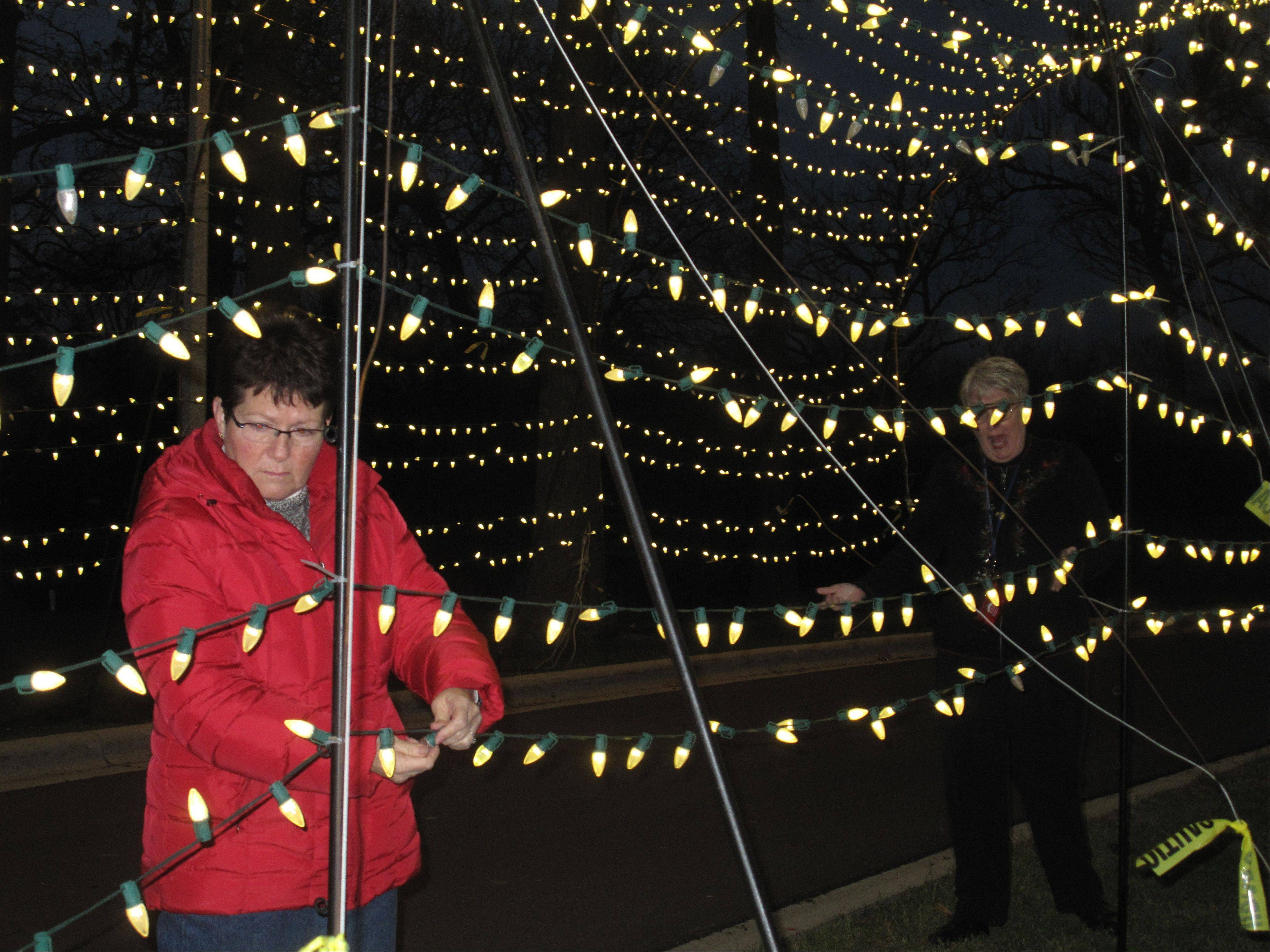 Pam Bellm, a member of the Rotary Club of Aurora and a co-chairwoman of the Festival of Lights, fixes a light on the tunnel display, which she says is always a favorite among children.