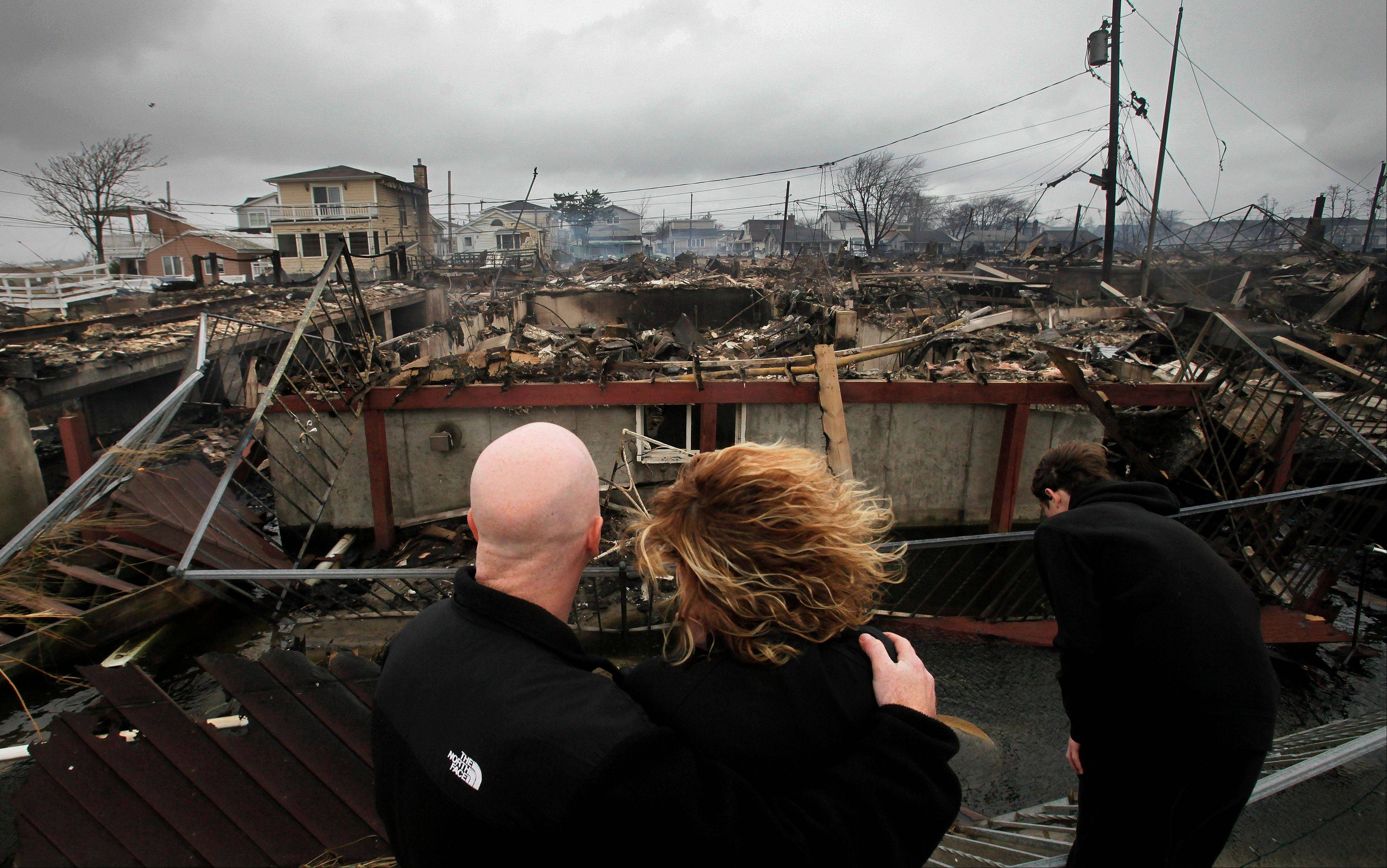 Robert Connolly, left, embraces his wife, Laura, as they survey the remains of the home owned by her parents that burned to the ground in the Breezy Point section of New York, during Superstorm Sandy. In Google's 12th annual roundup of trending searches, Superstorm Sandy, the damaging storm that knocked out power and flooded parts of the East Coast in the midst of a U.S. presidential campaign, was third.