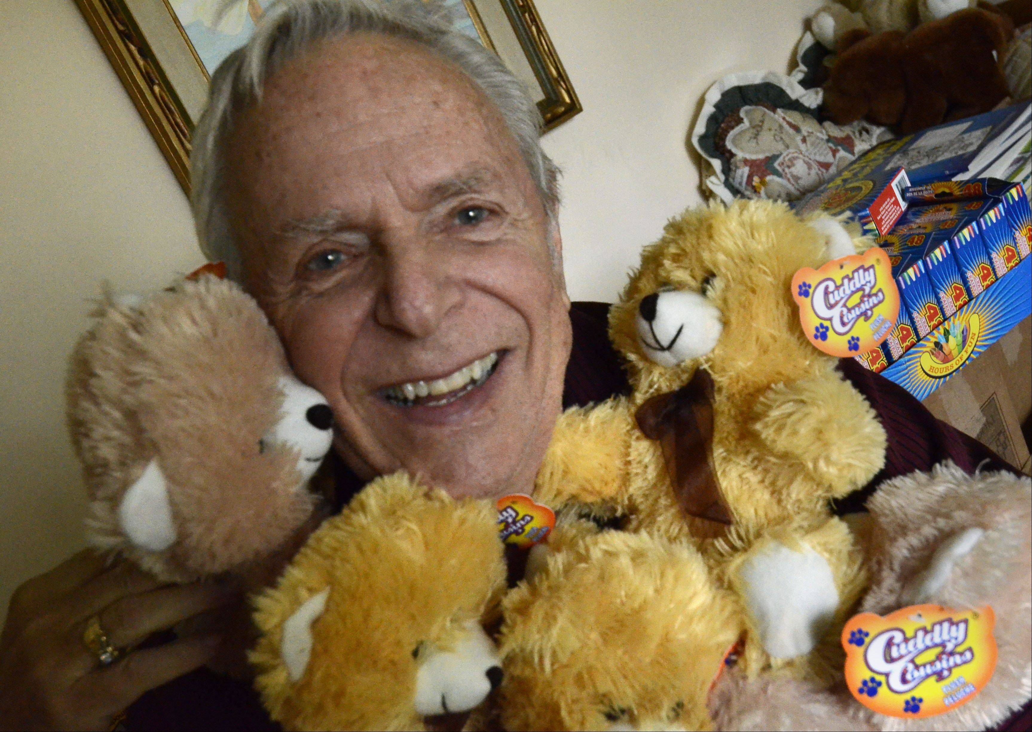 Jim Harney gives a hug to some of the teddy bears that will given to children this year.
