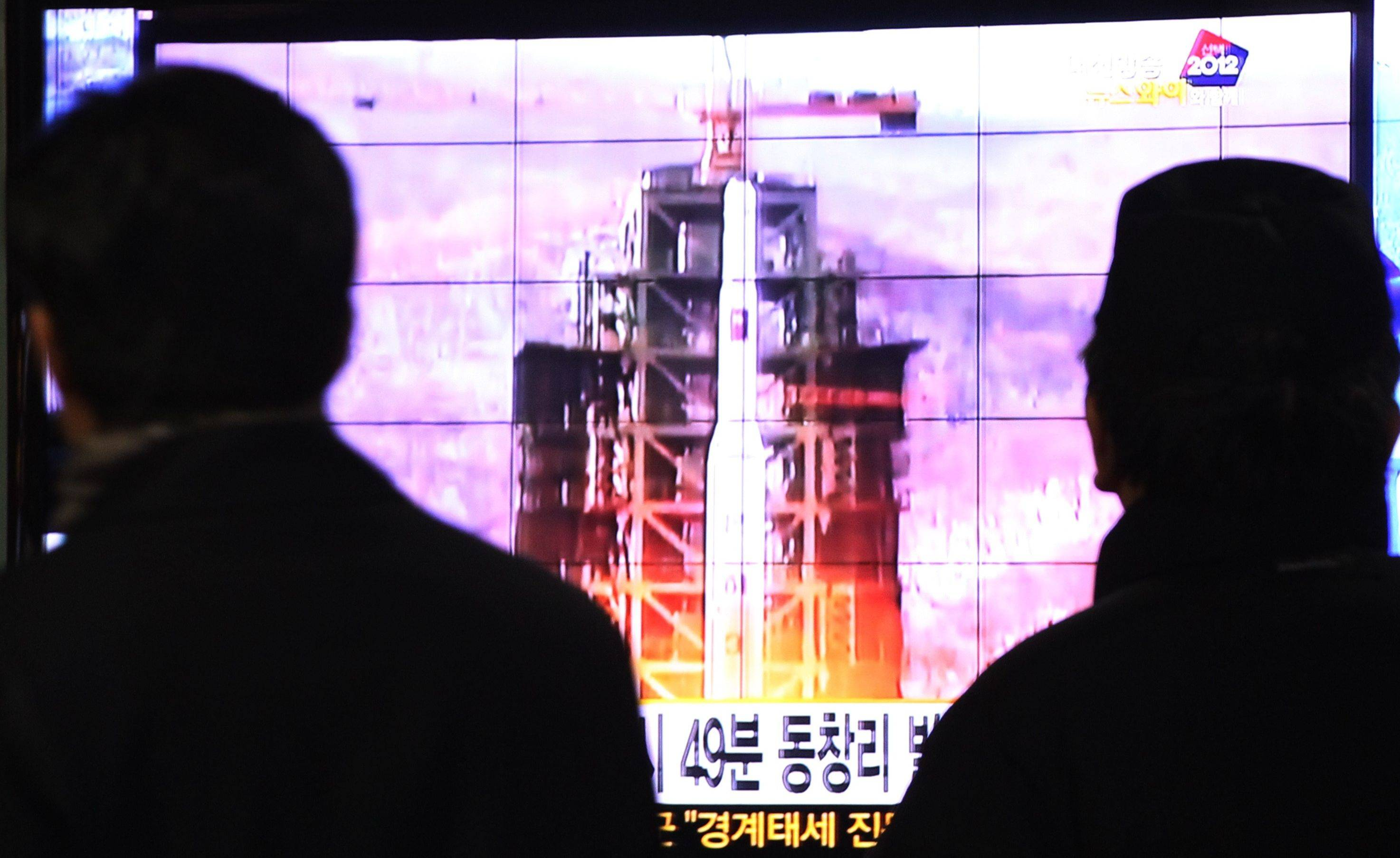 South Koreans at a Seoul railway station watch a TV news account of the launch of a North Korean rocket Wednesday.
