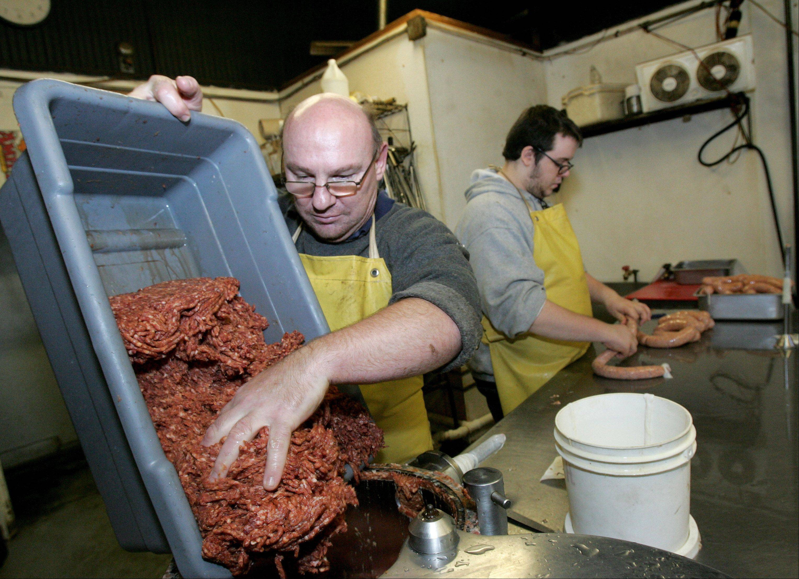 Wurst Kitchen employees Clemens Hog and Matt Tigges make hot Italian sausage, one of more than 80 kinds of sausage the shop makes.