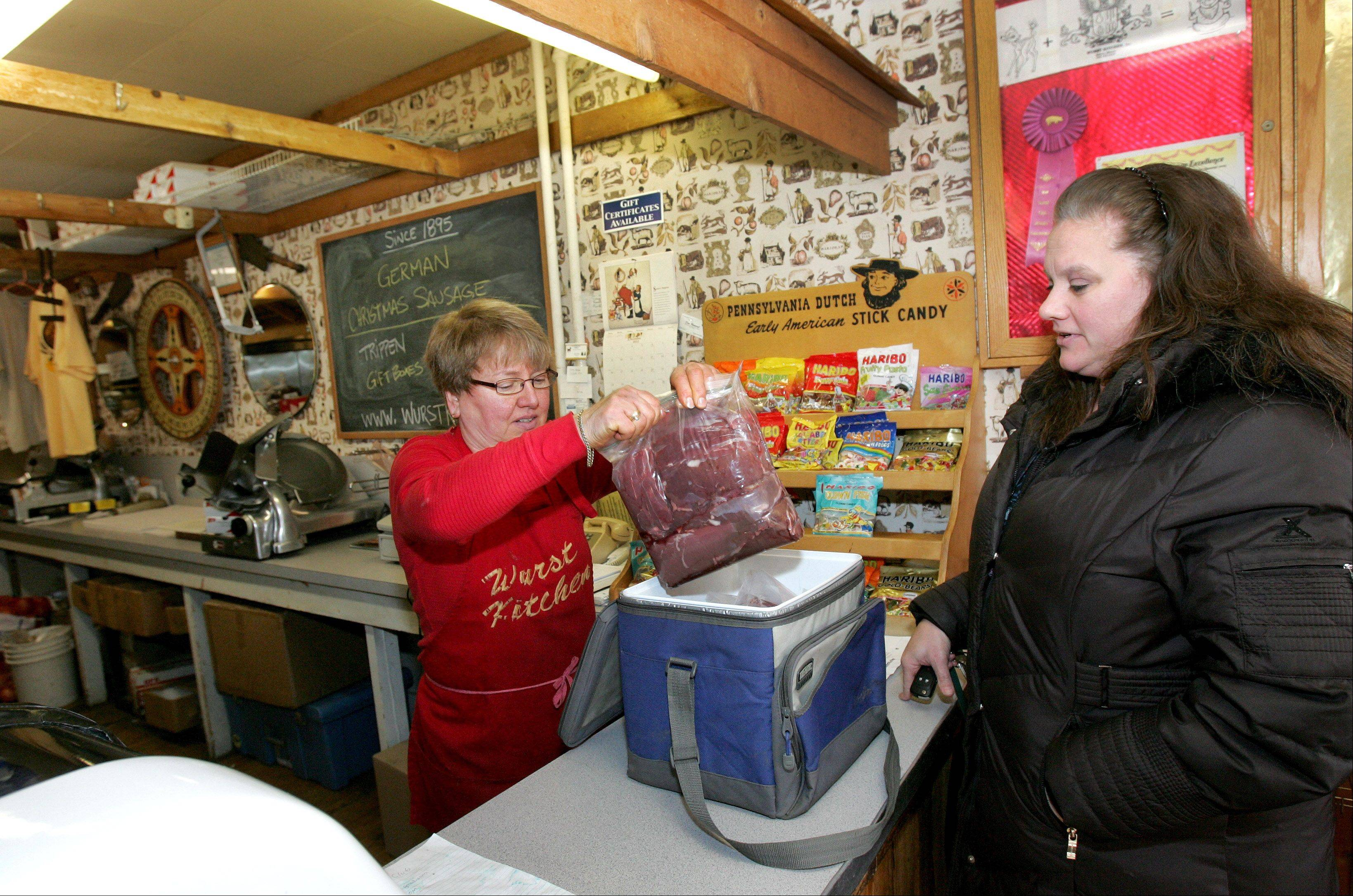 Irmy Gohs, left, takes some venison from customer Christine Cates of DeKalb to make into meat sticks. The store is a favored place for hunters to have their meat processed.