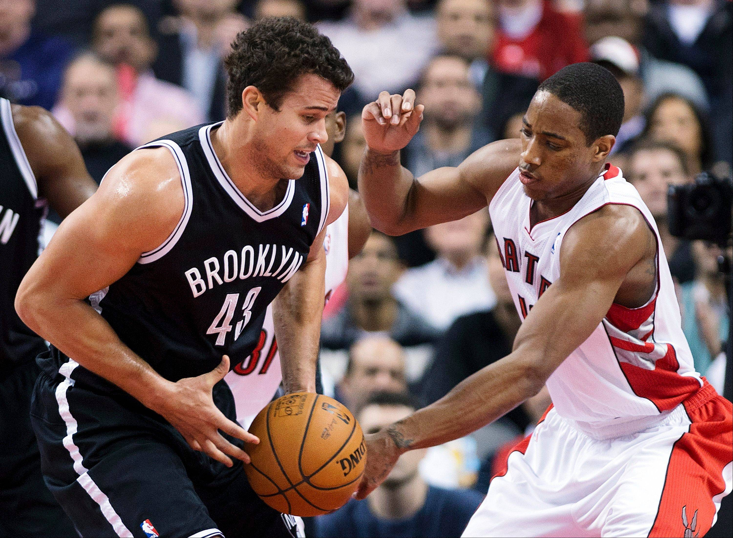 Toronto Raptors forward DeMar DeRozan, right, battles for the ball against Brooklyn Nets forward Kris Humphries, left, Wednesday during the first half in Toronto.