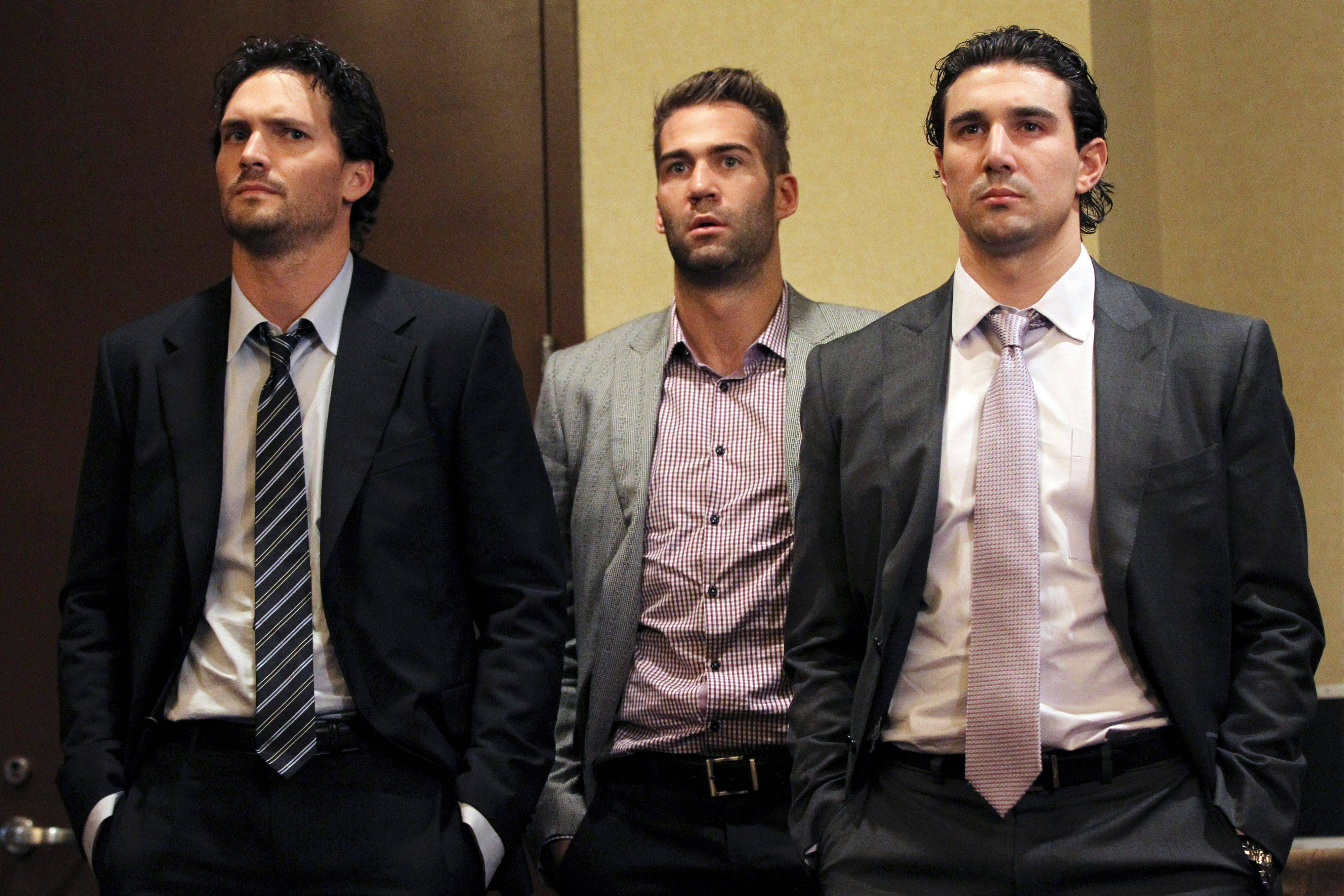 Winnipeg Jets' Ron Hainsey, left, Anaheim Ducks' Daniel Winnik, center, and free agent Chris Campoli listen to NHL Commissioner Gary Bettman and deputy commissioner Bill Daly last week in New York.