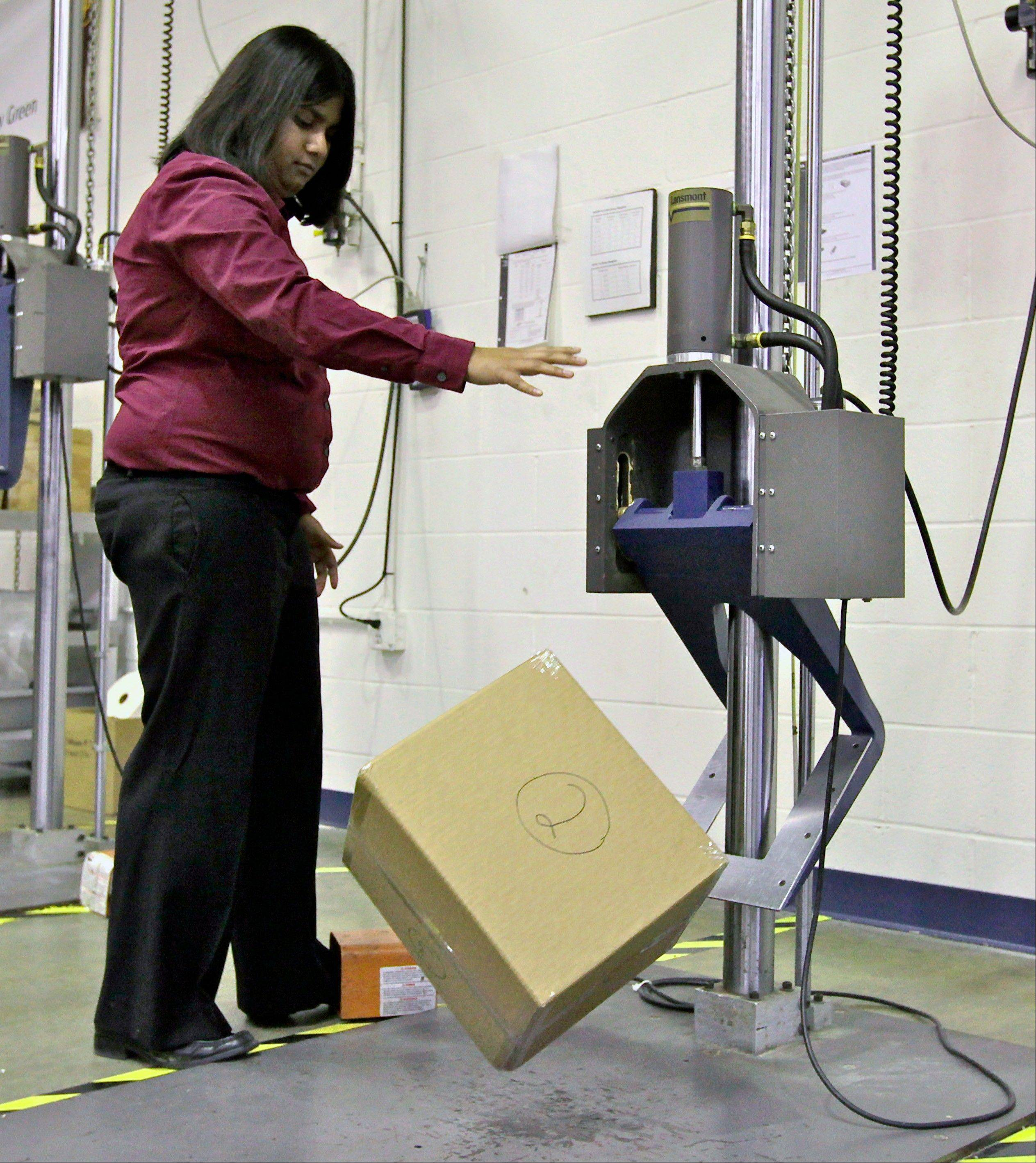 UPS packaging engineer Preeti Agrawal tests a packed box using a drop impact tester that simulates a box traveling through the small parcel system at the UPS Package Design and Testing Lab in Addison.