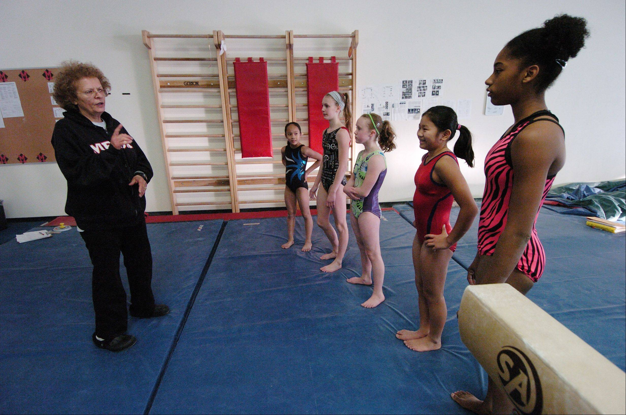 JOE LEWNARD/jlewnard@dailyherald.com Gymnastics coach Ileana Albu works with pupils during a session at Midwest Elite Gymnastics Academy in South Barrington. The academy will be moving to Elgin in January.