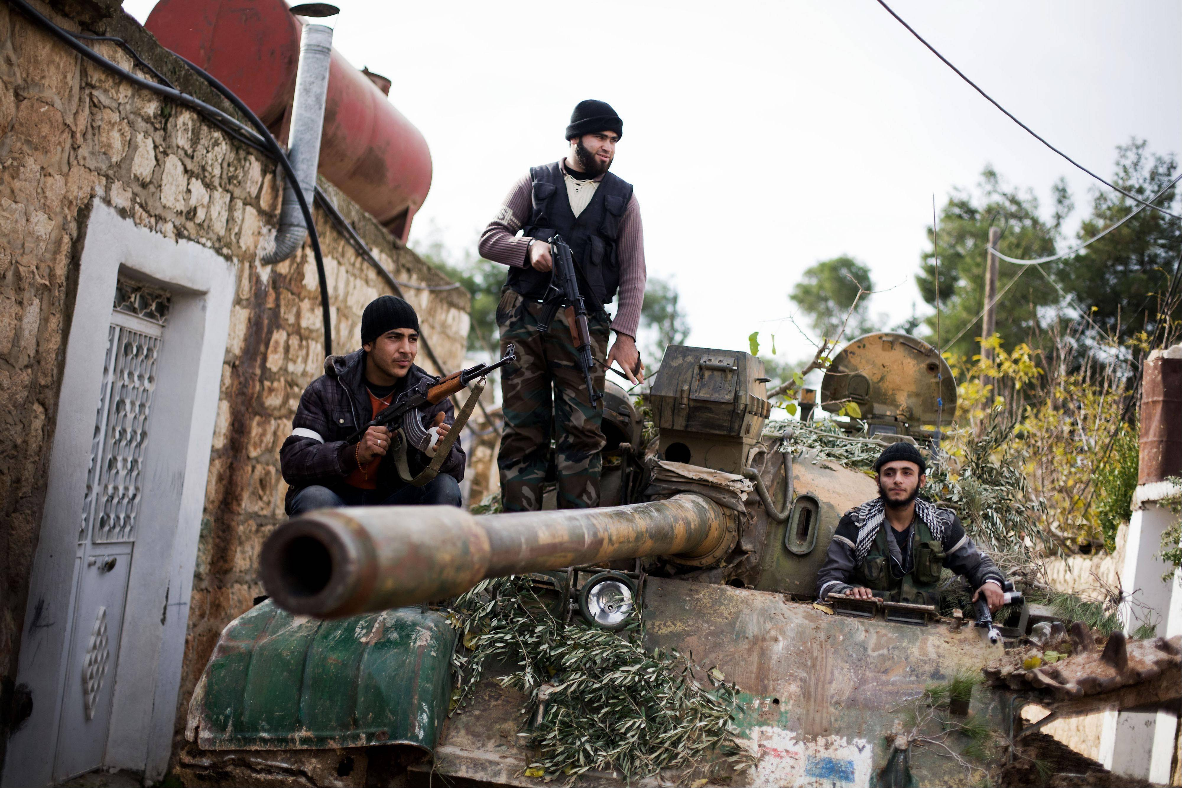 Kurdish members of the FSA are seen on a tank stolen from the Syrian Army in Fafeen village, north of Aleppo province, Syria, Wednesday.
