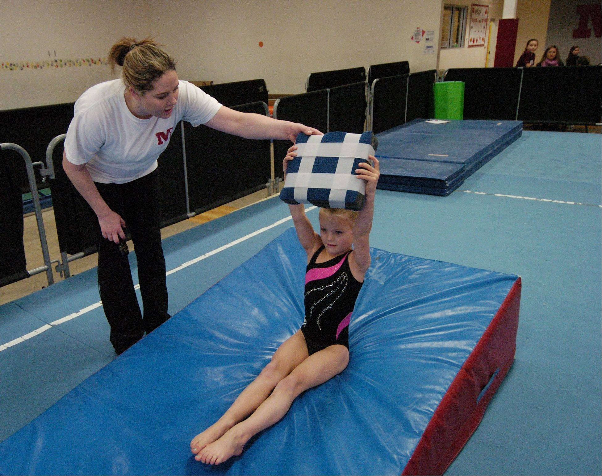 JOE LEWNARD/jlewnard@dailyherald.comGymnastics coach Caitlin Summerville works with Annika Jessie, 5, of Schaumburg at Midwest Elite Gymnastics Academy in South Barrington. The academy will be moving to Elgin in January.