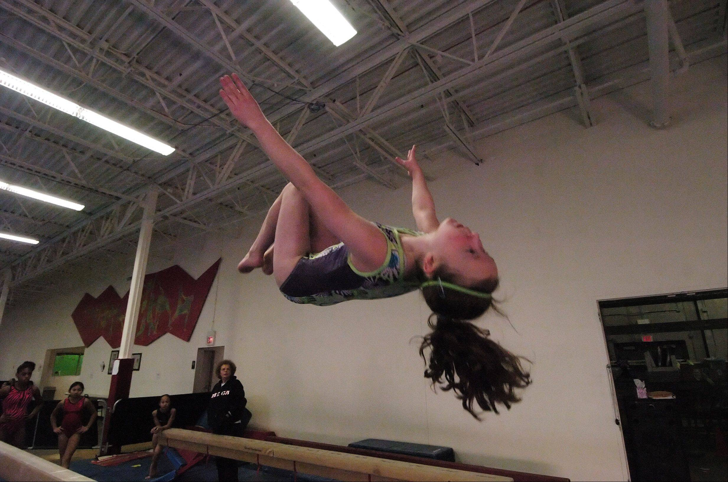 Sandie Merena, 11, of Elgin practices her dismount from the balance beam at Midwest Elite Gymnastics Academy in South Barrington. The academy will be moving to Elgin in January.