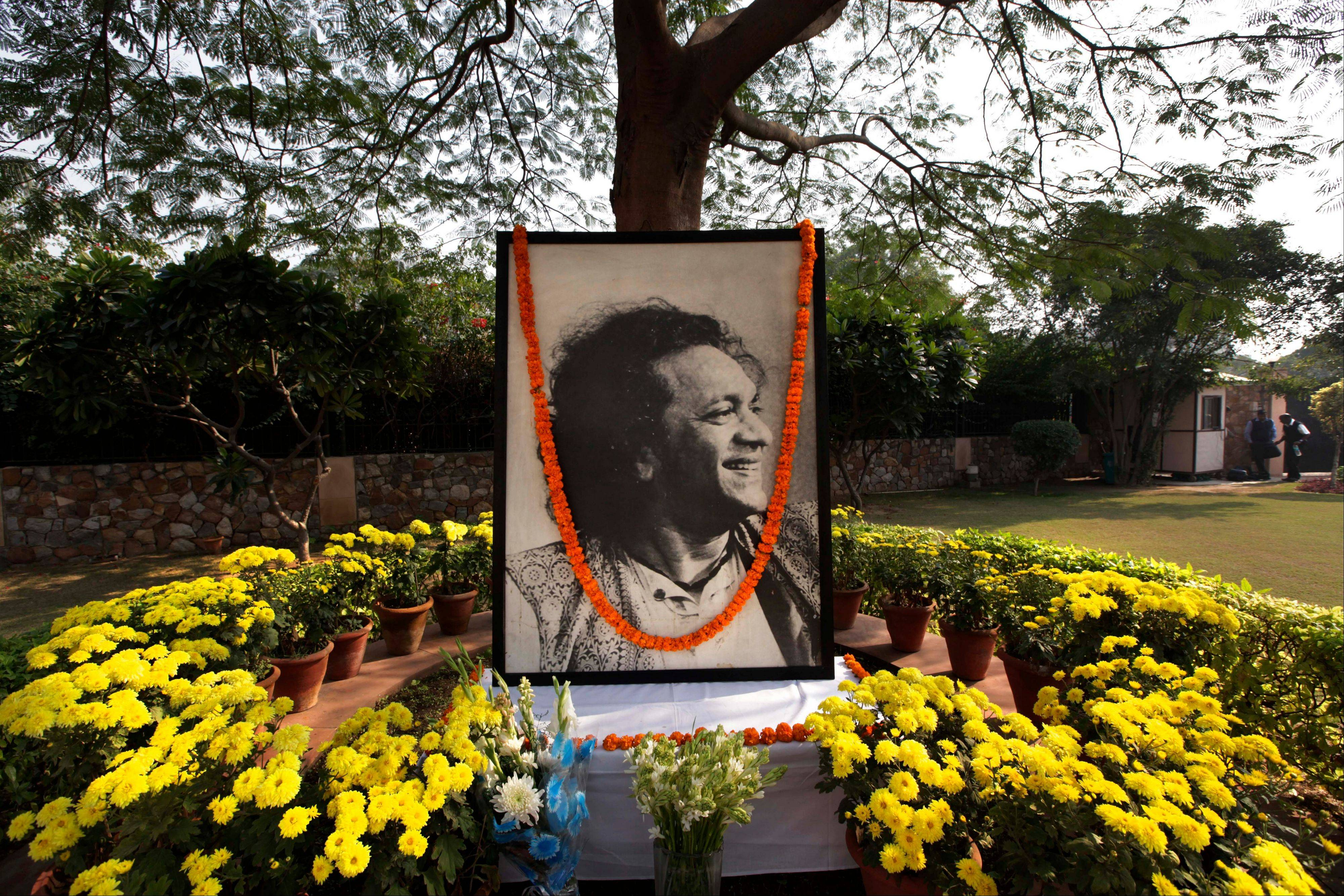 A portrait of legendary Indian sitar player Ravi Shankar is placed under a tree Wednesday as part of a makeshift memorial at his music center, in New Delhi, India. Shankar, who is credited with connecting the world to Indian music, died Tuesday in San Diego at the age of 92.