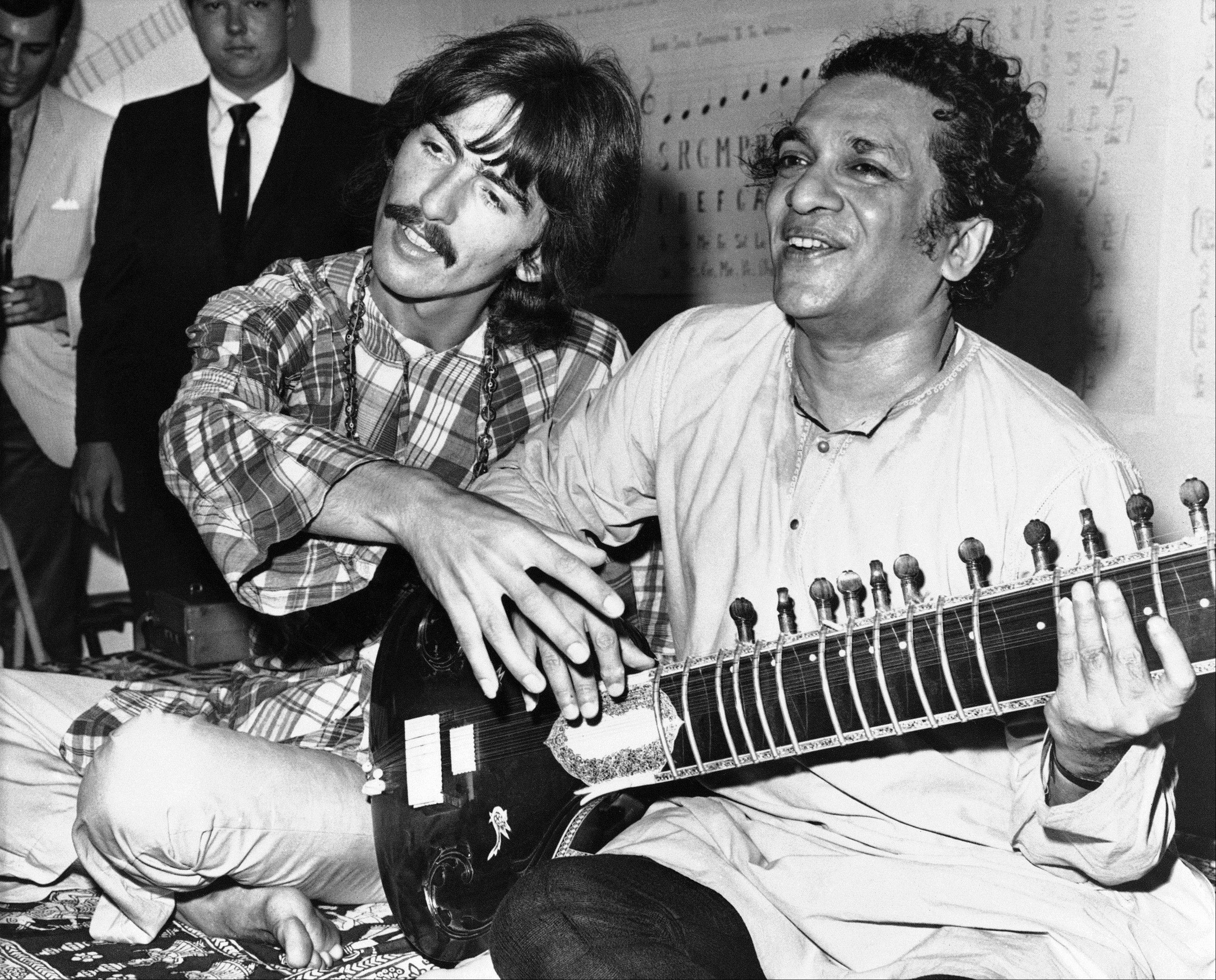 In this Aug. 3, 1967 file photo, George Harrison, of the Beatles, left, sits cross-legged with his musical mentor, Ravi Shankar of India, in Los Angeles, as Harrison explains to newsmen that Shankar is teaching him to play the sitar. Shankar, the sitar virtuoso who became a hippie musical icon of the 1960s after hobnobbing with the Beatles and who introduced traditional Indian ragas to Western audiences over an eight-decade career, died Tuesday. He was 92.