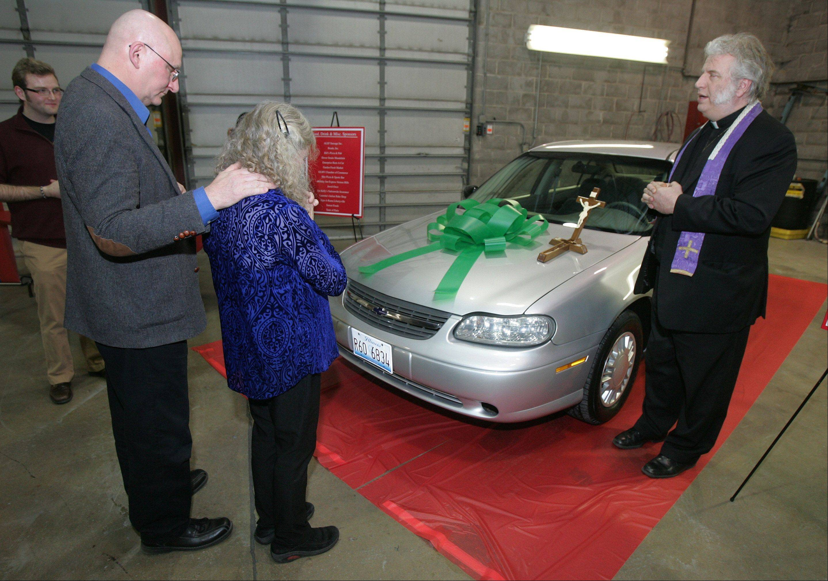 Gilbert R. Boucher II/gboucher@dailyherald.comGeoff and Marita Kovarik, of Mundelein, pray as the car they were given is blessed by Father Gerald O'Reilly Thursday as part of CARSTAR's 2nd Annual Recycled Rides Program. The Kovarik family were the recipients this year by the company that gives away a rebuilt car to a needy family for the holidays.
