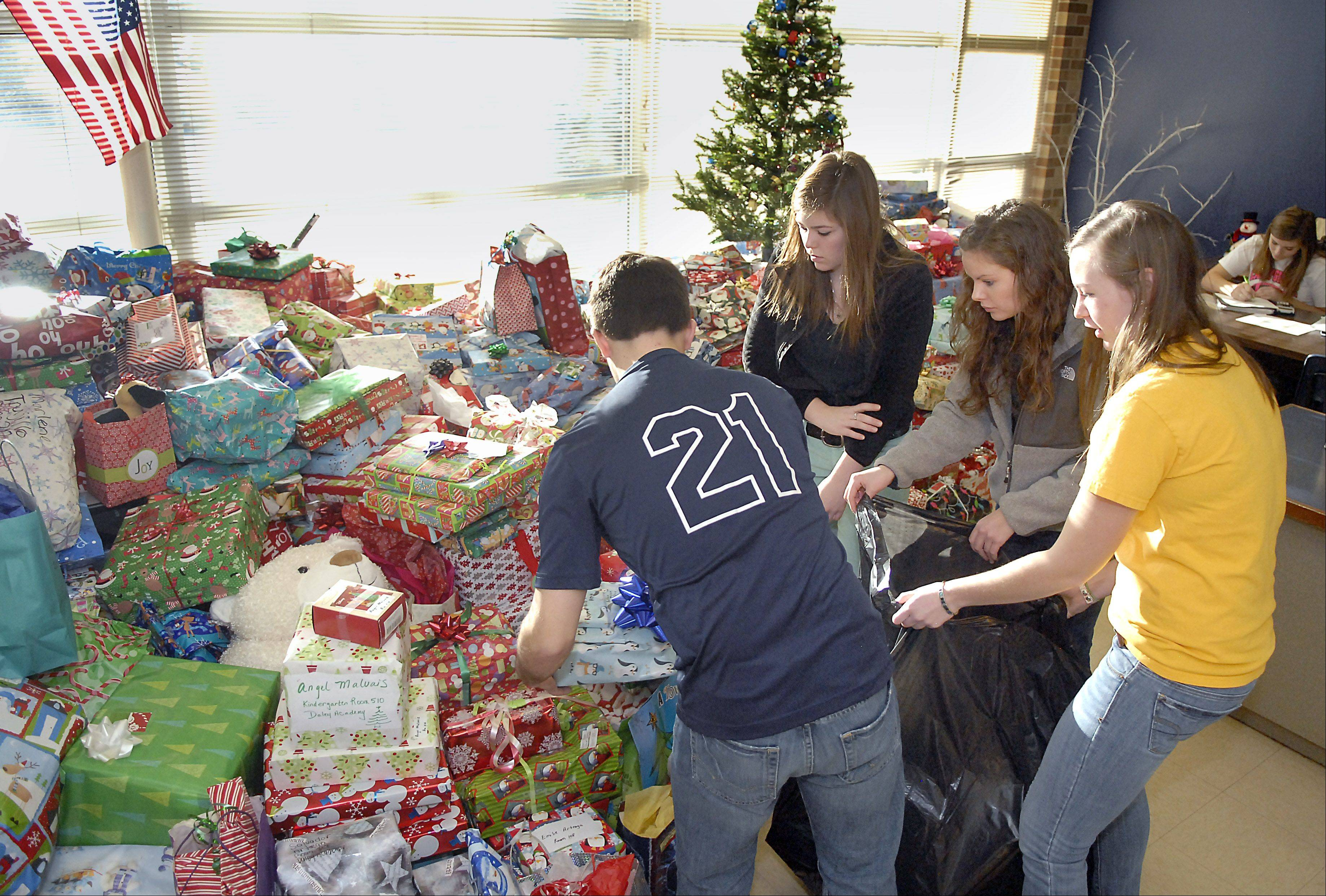 Cary-Grove High School students and Interact Club members Patrick Kelly, 18, Peyton Taylor, 16, Rita O'Connell, 18, and Christine Sweinberg, 17, bag presents Thursday to be loaded on a Chicago Public Schools truck bound for the Richard J. Daley Academy in the Back of the Yards neighborhood.