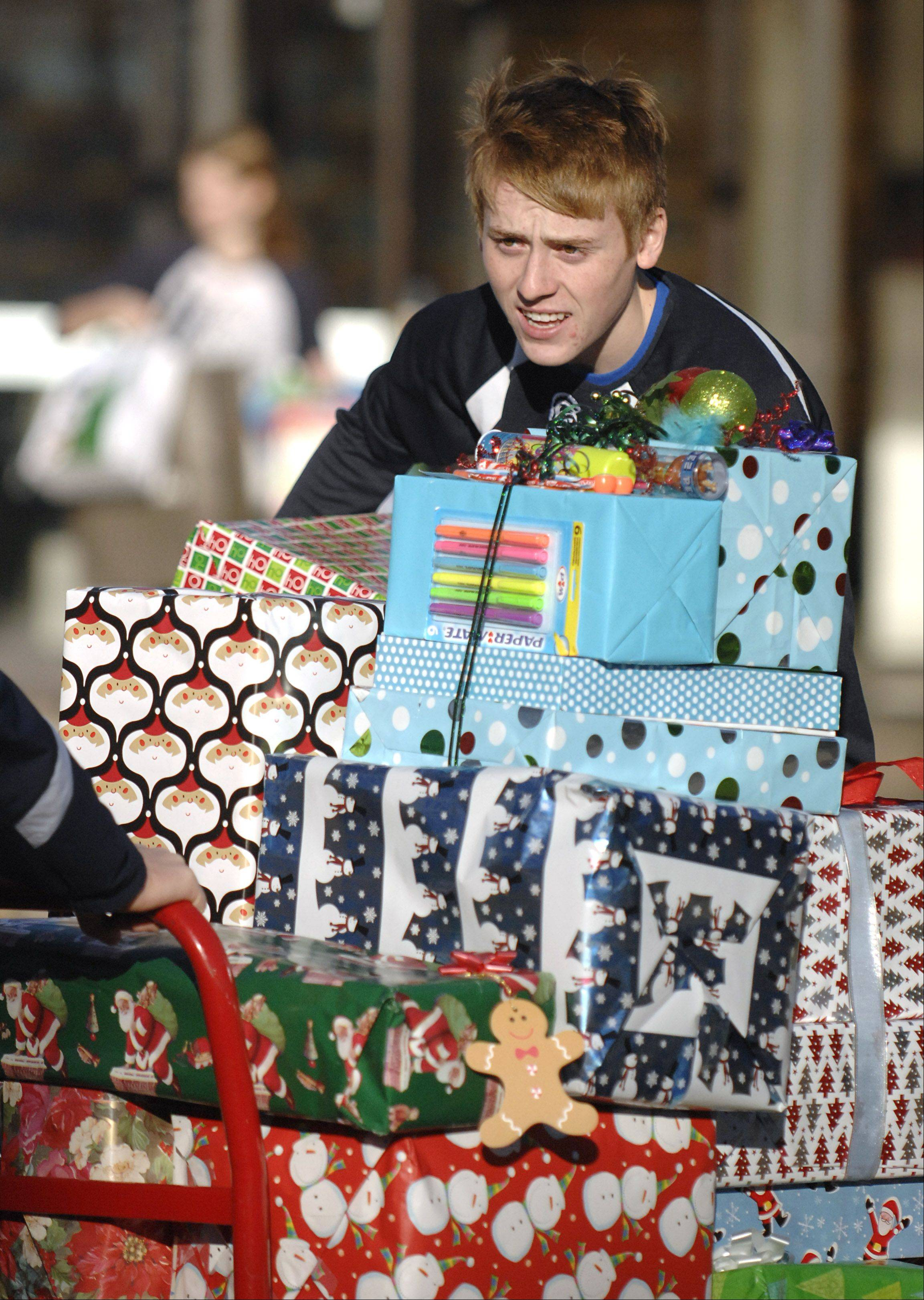 Cary-Grove High School student Brian O'Connor, 17, steadies a push cart full of donated presents while a classmate pulls it to the truck bound Thursday for the Richard J. Daley Academy in the Back of the Yards neighborhood in Chicago.