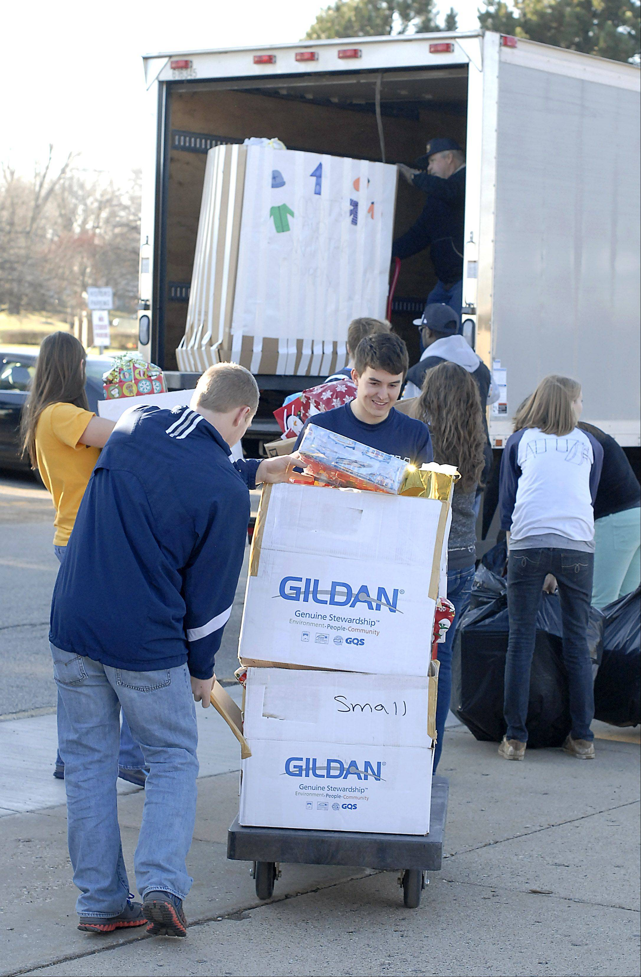 Cary-Grove High School students Matt Hughes, 16, and Patrick Kelly, 18, guide a push cart full of presents toward a truck bound Thursday for the Richard J. Daley Academy in Chicago. Kelly is president of the Interact Club, which gathered about $20,000 worth of presents for kids at the Academy.