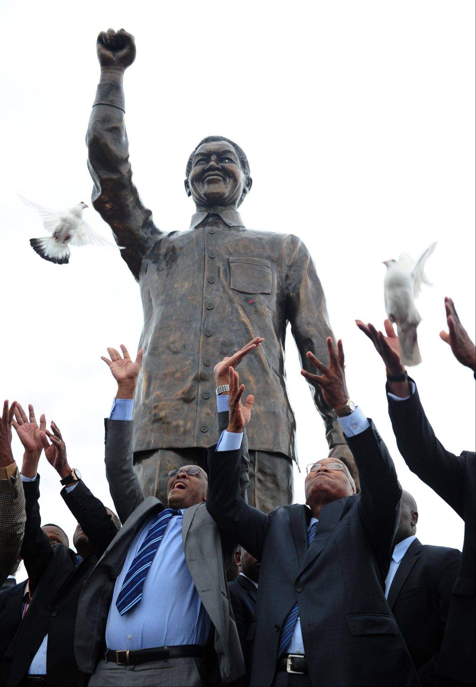 Doves are released after a giant statue of former President Nelson Mandela was unveiled on Naval Hill in Bloemfontein, South Africa, Thursday, Dec 13, 2012, by President Jacob Zuma, front right, ahead of the ruling African National Congress's elective conference. Mandela, who has been hospitalized since the weekend, is recovering from a lung infection.
