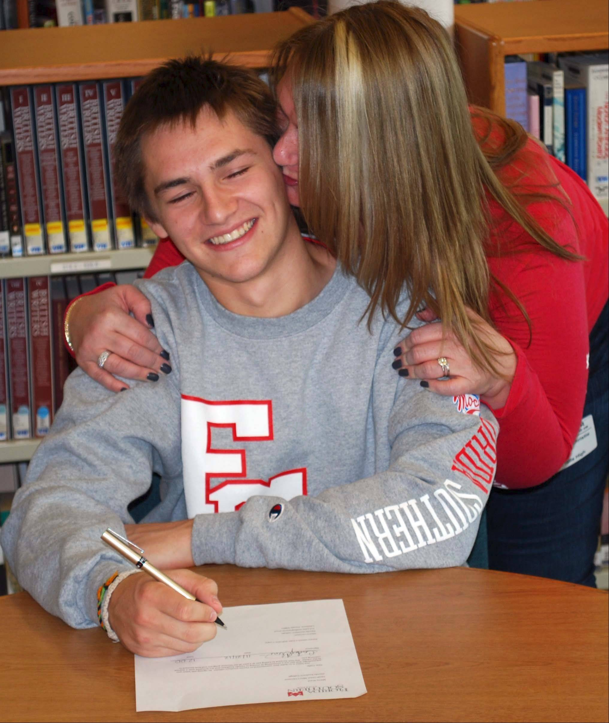Vernon Hills senior goalie Cody Christie is kissed by his mother, Annie Christie-Patrick, after signing his letter of intent to play lacrosse for Florida Southern College. Christie is the first Division II lacrosse player to come out of Vernon Hills.