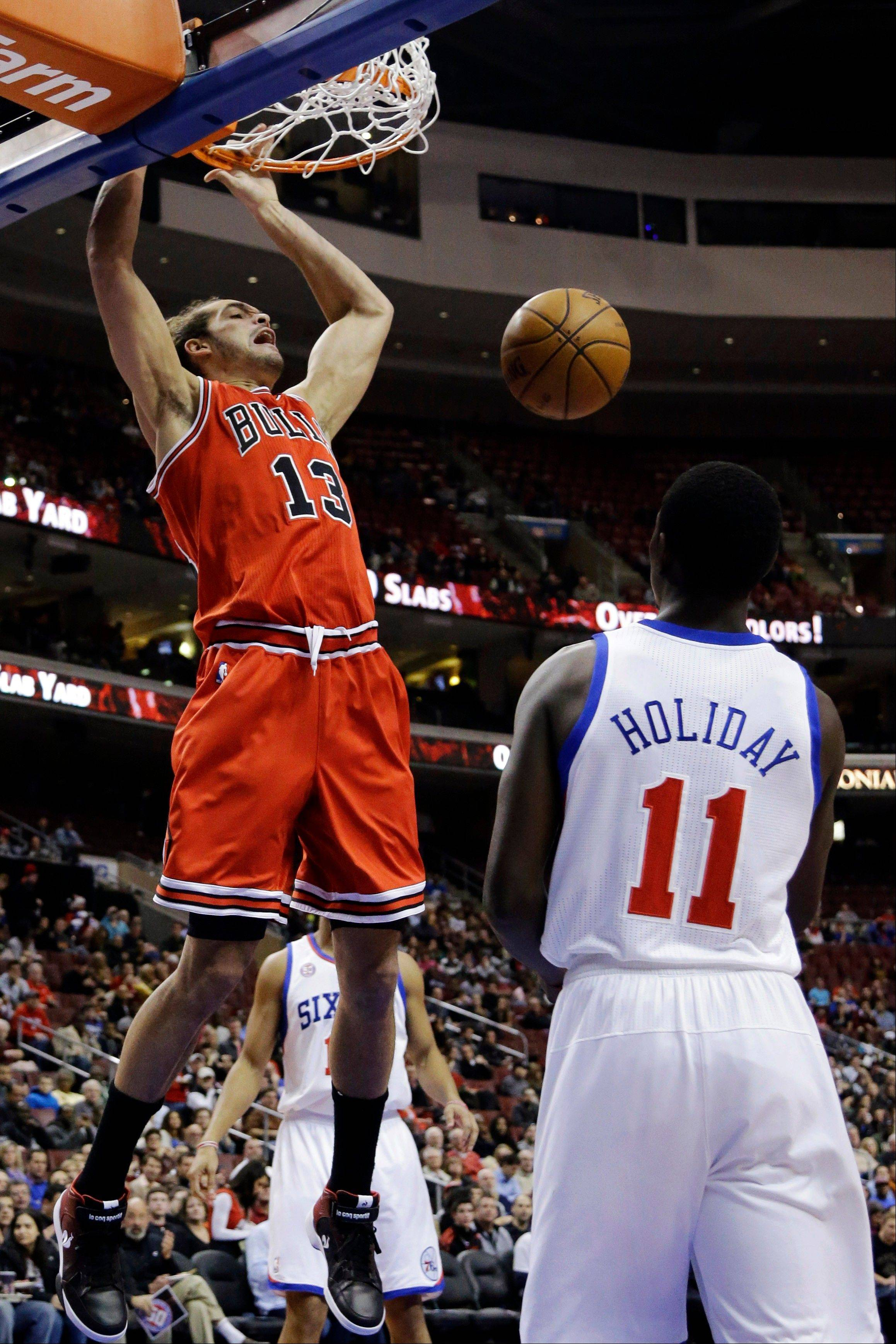 Chicago Bulls' Joakim Noah (13) dunks the ball as Philadelphia 76ers' Jrue Holiday (11) watches during the first half of an NBA basketball game, Wednesday, Dec. 12, 2012, in Philadelphia.