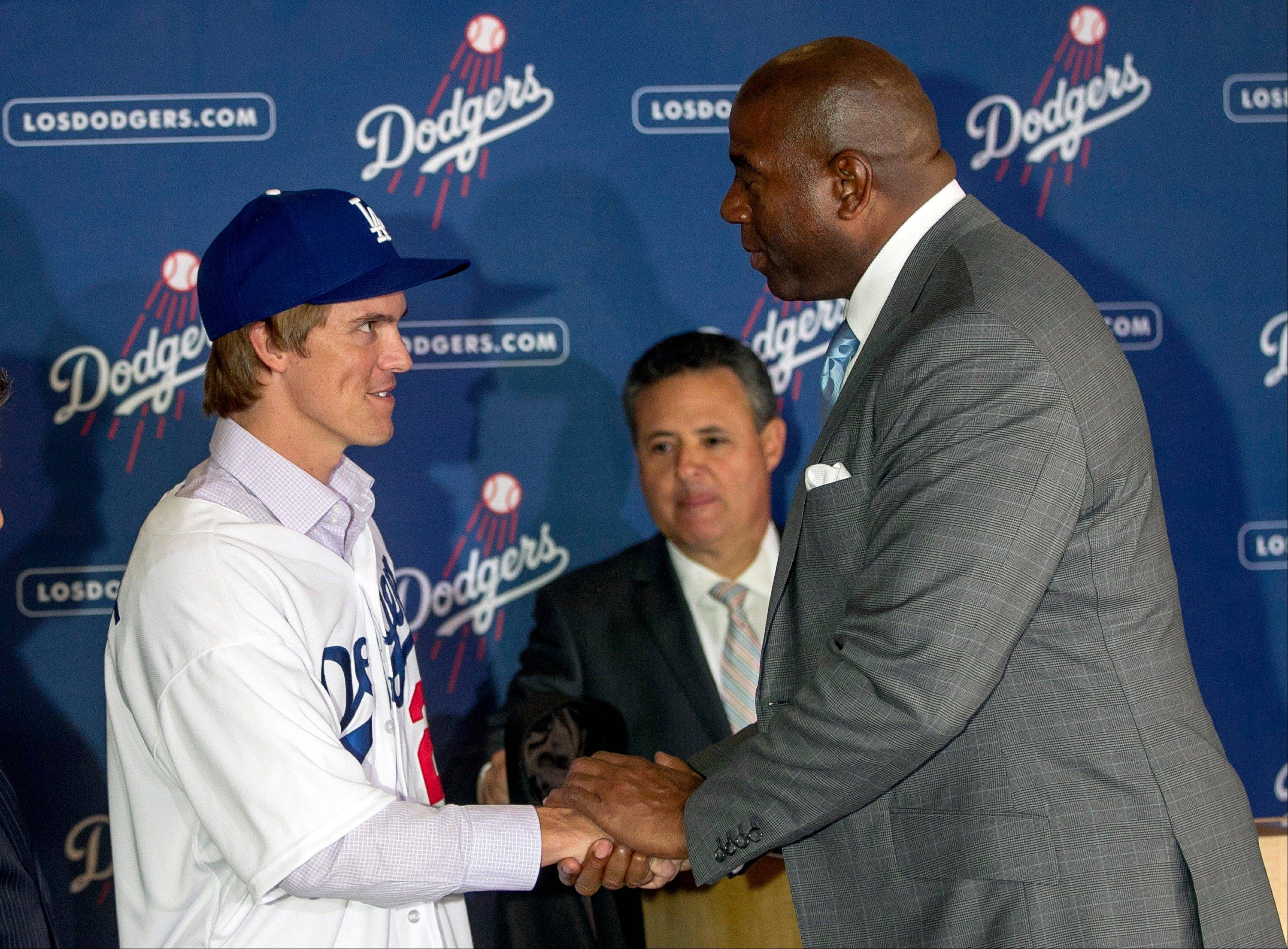 New Los Angeles Dodgers pitcher Zack Greinke, left, shakes hands with co-owner Magic Johnson during a news conference announcing his $147 million, six-year contract Tuesday.