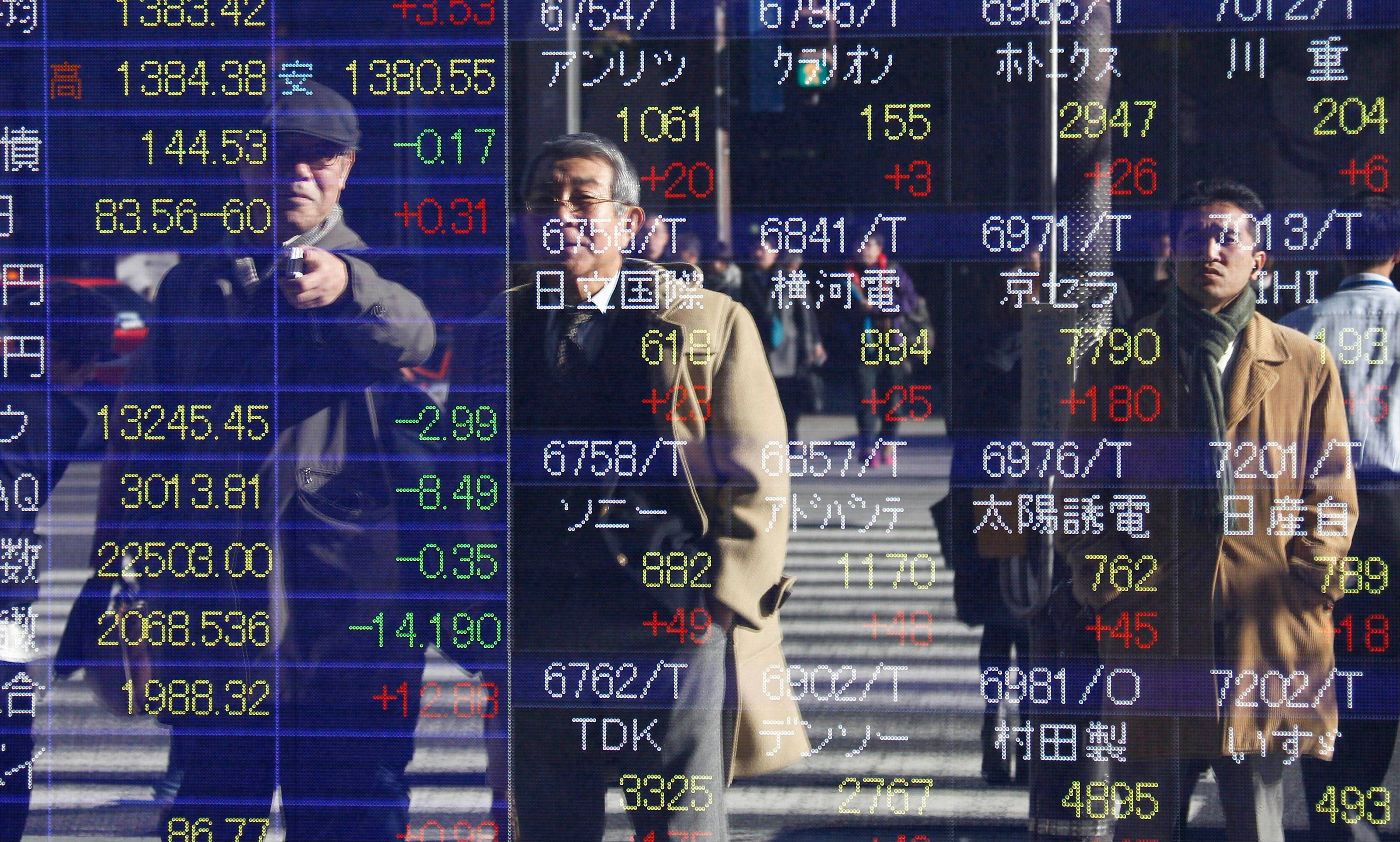 People are reflected on the electronic board of a securities firm in Tokyo Thursday.