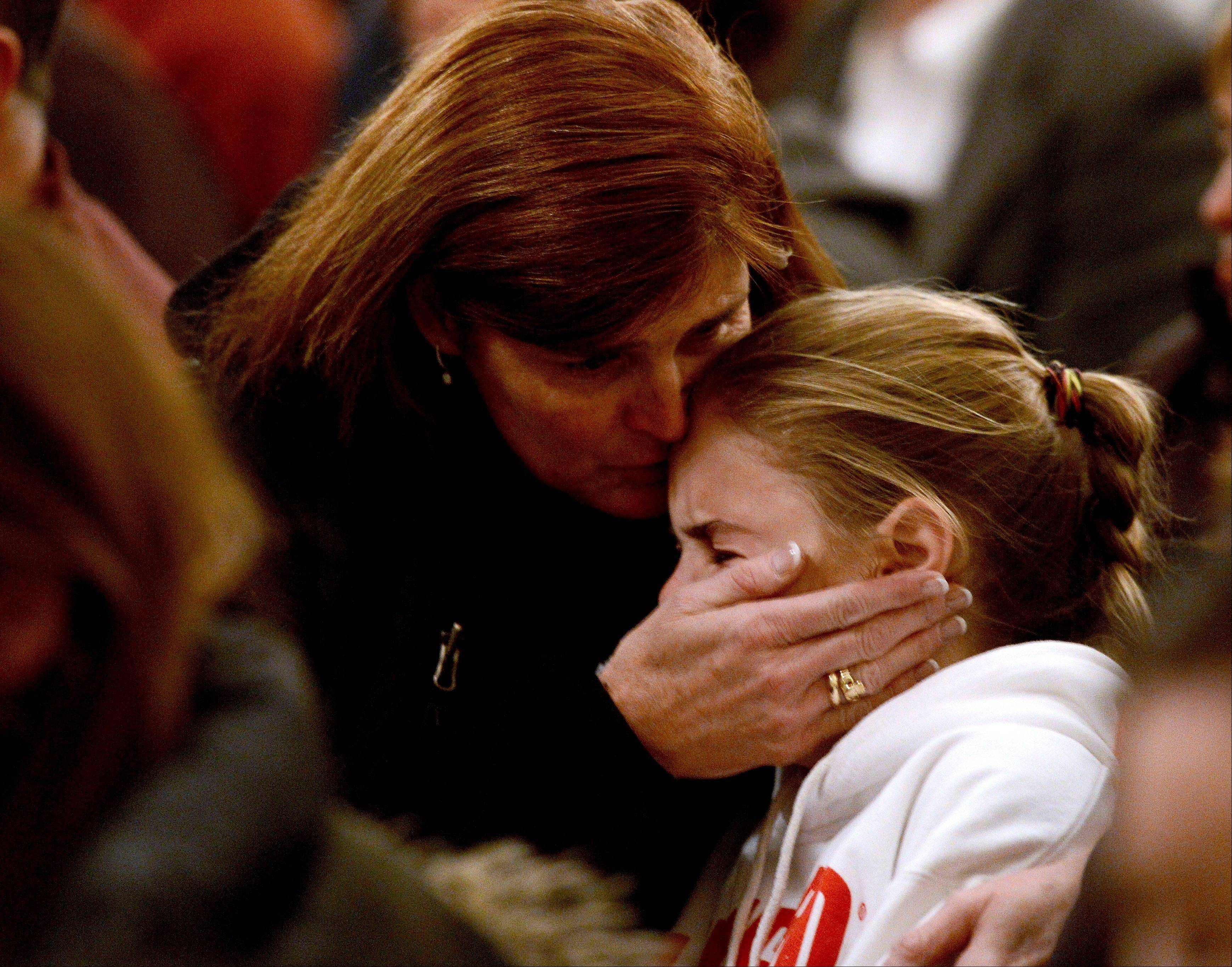 A woman comforts a young girl during a vigil service Friday for victims of the Sandy Hook Elementary shooting, at St. Rose of Lima Roman Catholic Church in Newtown, Conn.
