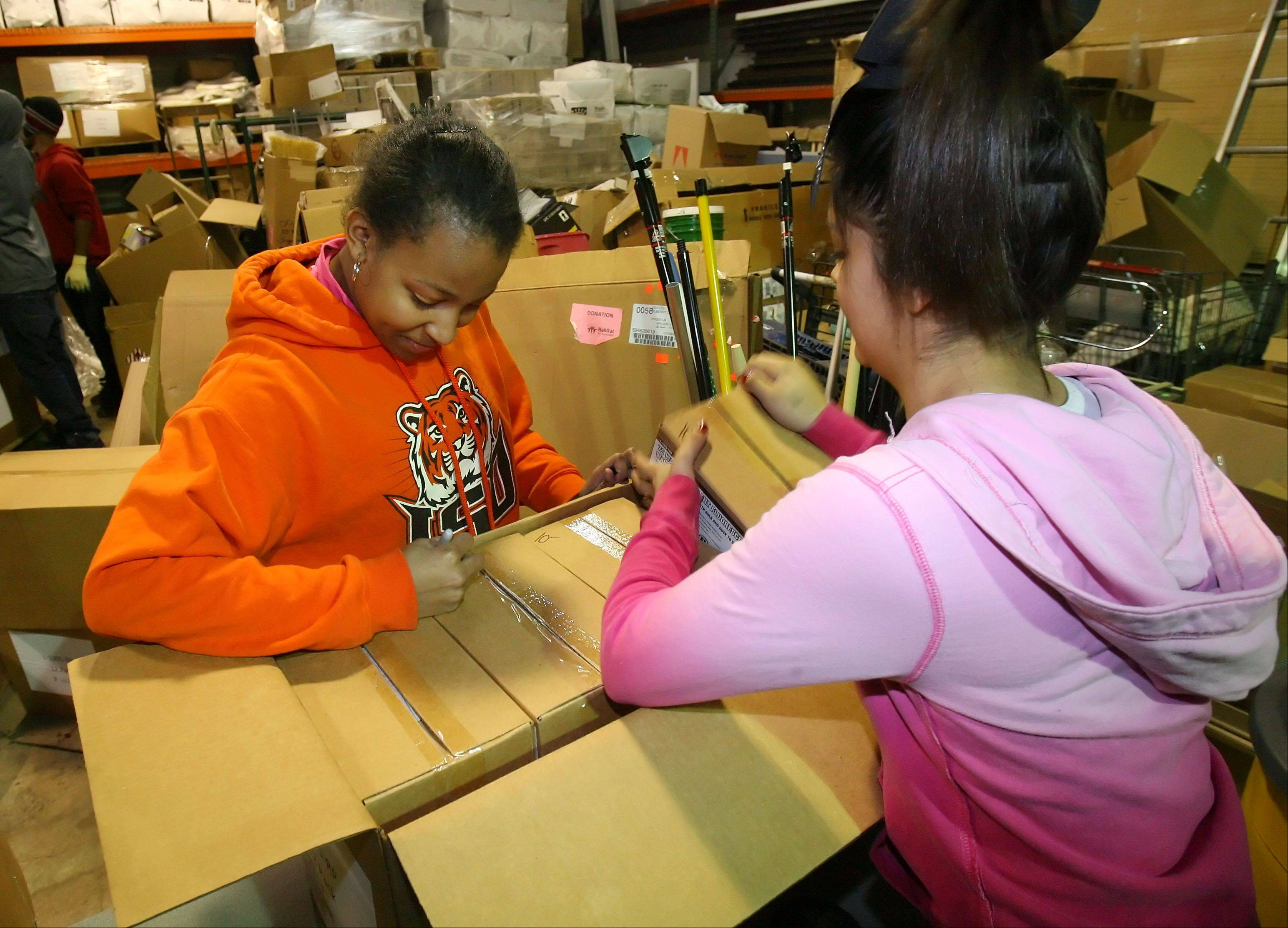 Mundelein High School sophomores Mariah Ruff, left, and Jazmine Rivera label boxes of fluorescent bulbs Friday at ReStore in Gurnee.