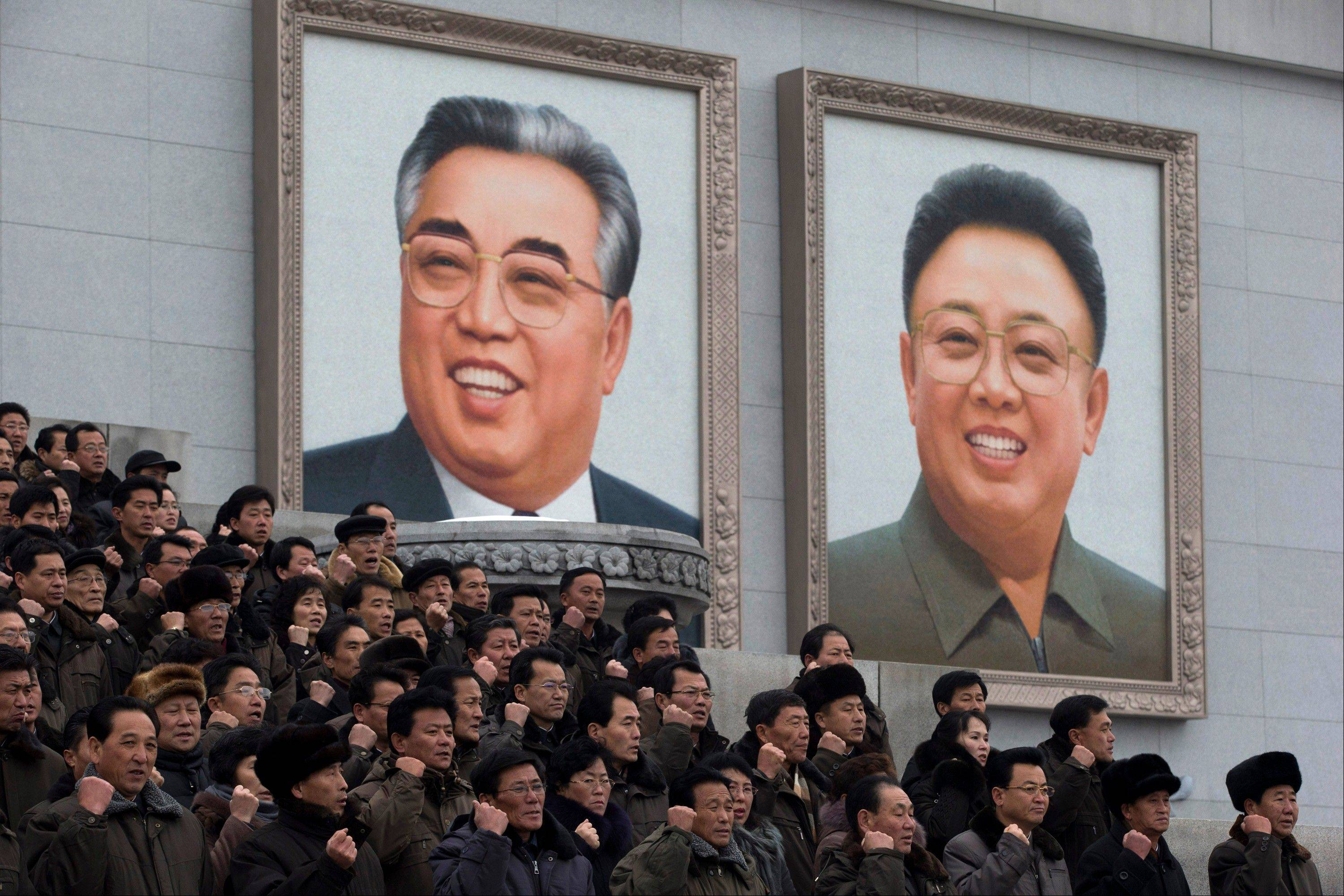 North Koreans chant slogans and gesture to show their determination near giant portraits of the late leaders Kim Il Sung, left, and Kim Jong Il during a mass rally organized to celebrate the success of a rocket launch that sent a satellite into space, on Kim Il Sung Square in Pyongyang, North Korea, Friday, Dec. 14, 2012.