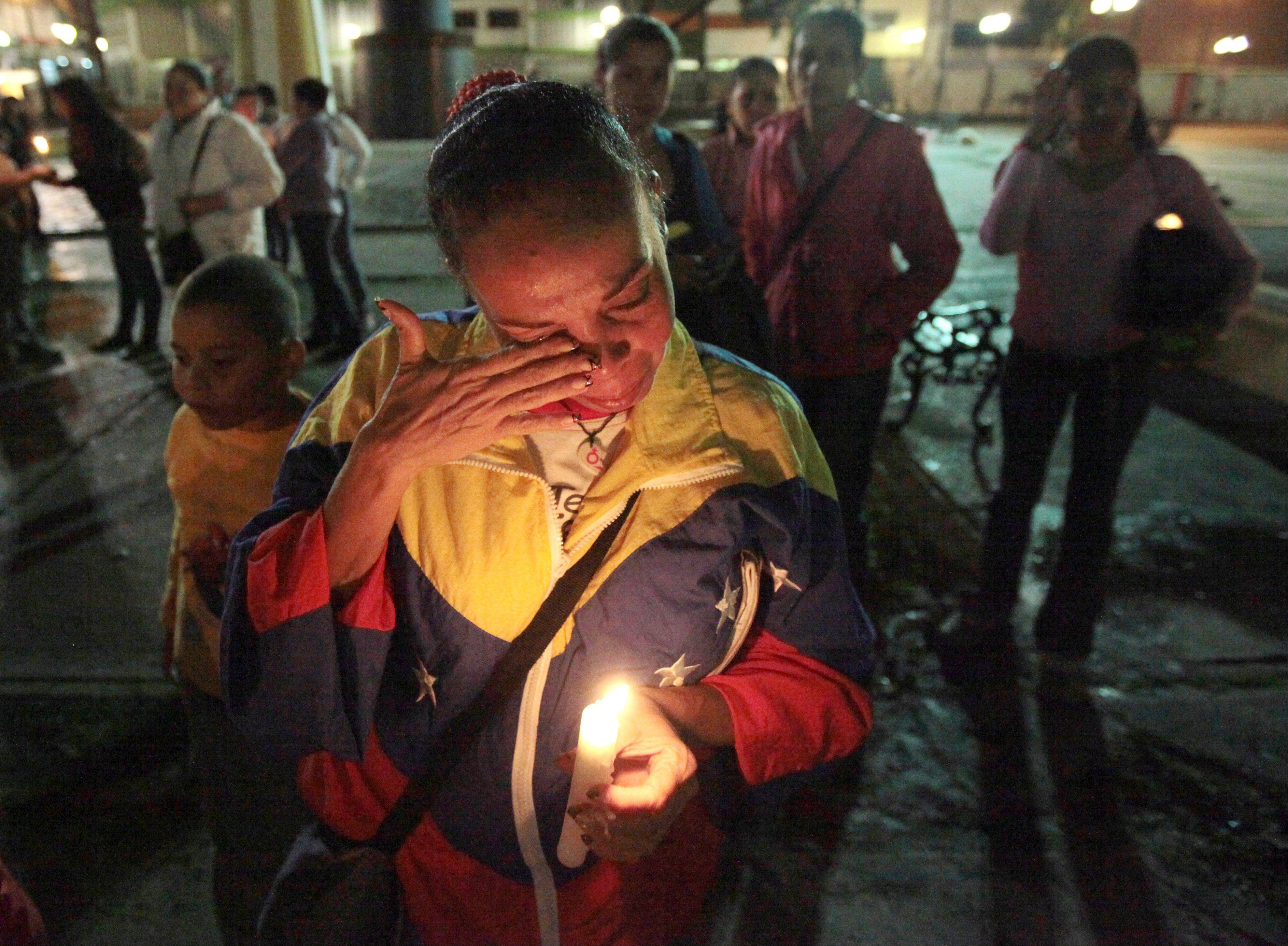 A woman holds a candle as she reacts during a vigil in support of Venezuela's President Hugo Chavez in Caracas, Venezuela, Thursday, Dec. 13, 2012. Chavez is recovering favorably despite suffering complications during cancer surgery in Cuba, his Vice President Nicolas Maduro said Thursday amid uncertainty over the Venezuelan leader's health crisis and the country's political future.
