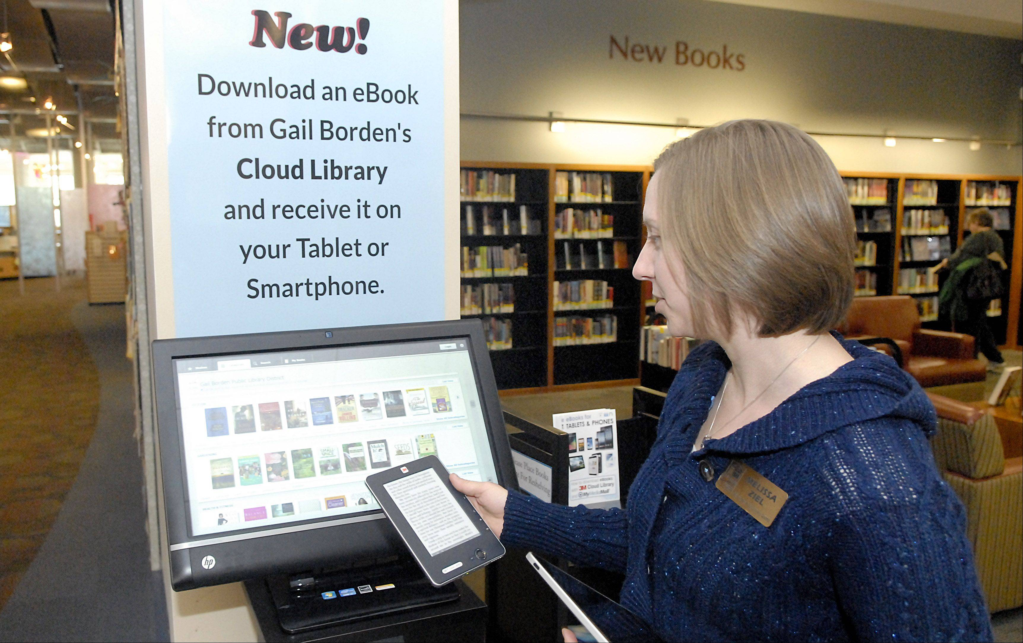 Melissa Ziel, Gail Borden Public Library's business librarian and e-book coordinator, demonstrates how to use the new 3M Cloud Library station, which allows people to download e-books wirelessly. The stations are located at the main library and the Rakow branch. $PHOTOCREDIT_ON$Laura Stoecker/lstoecker@dailyherald.com$PHOTOCREDIT_OFF$