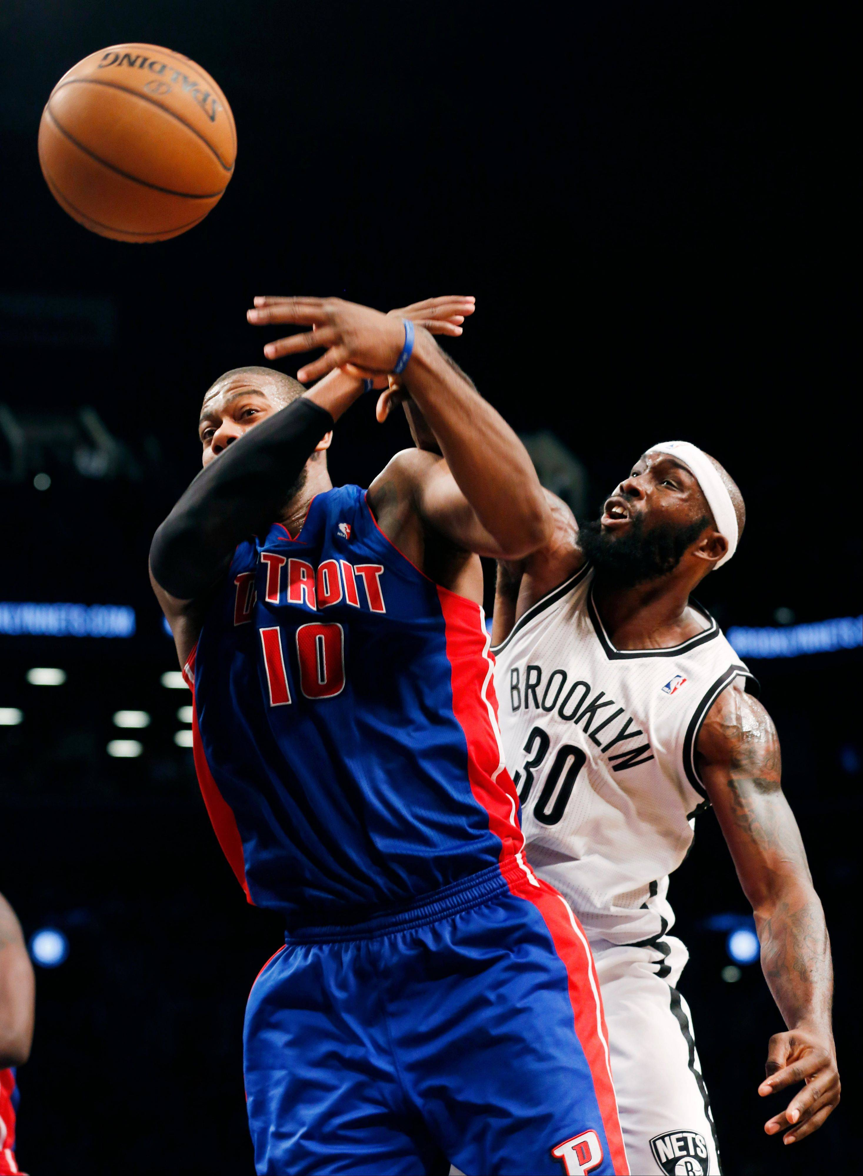 Pistons center Greg Monroe and the Nets� Keith Bogans battle for a rebound during Brooklyn�s 107-105 double overtime victory Friday night. Bogans will see his old team tonight when he returns to the United Center to take on the Bulls.